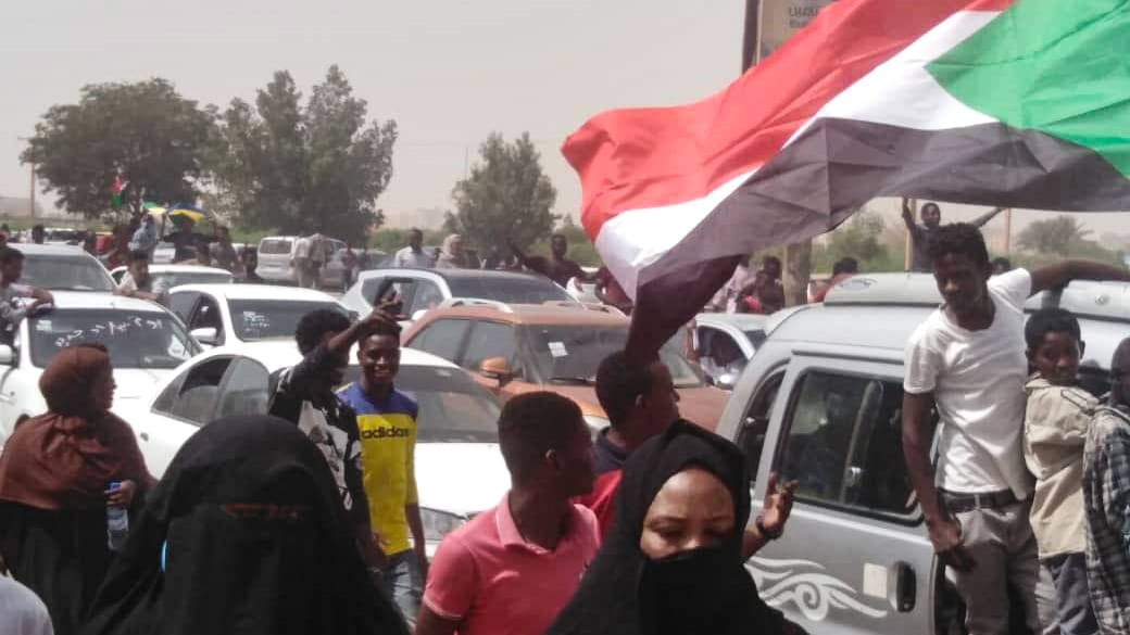 جنود سودانيون يقفون مع متظاهرين بالقرب من مقر الجيش بالخرطوم