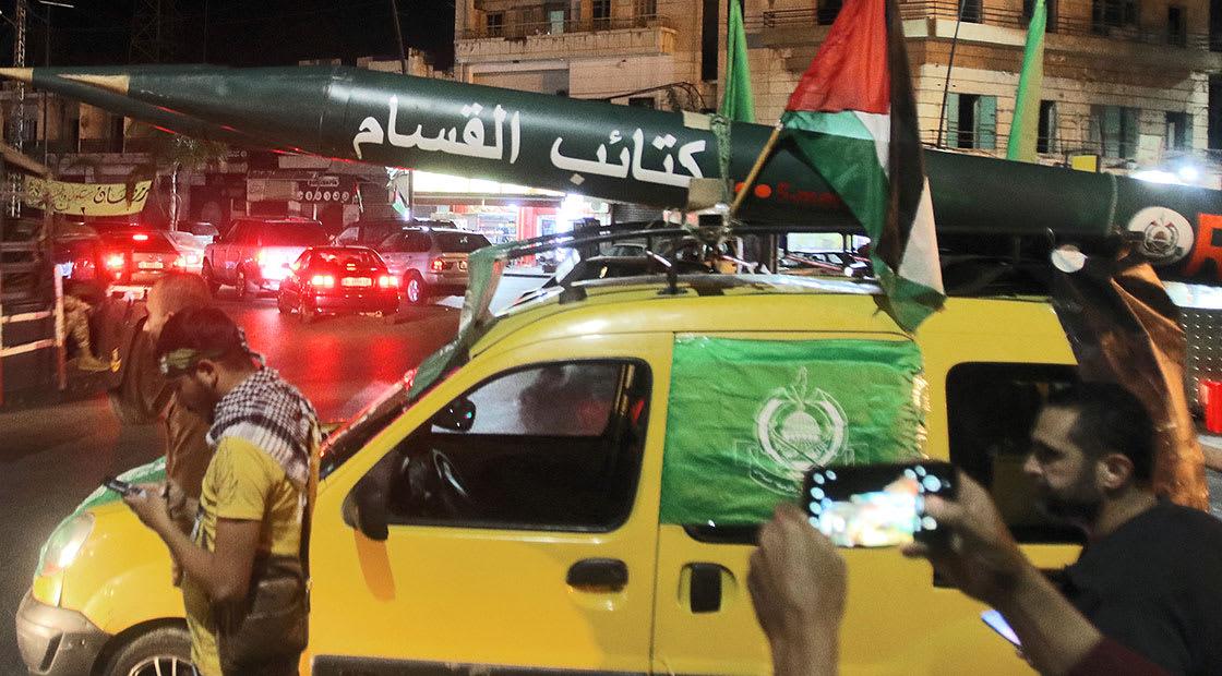رجل يستعرض مجسما لصاروخ القسام في غزة الثلاثاء