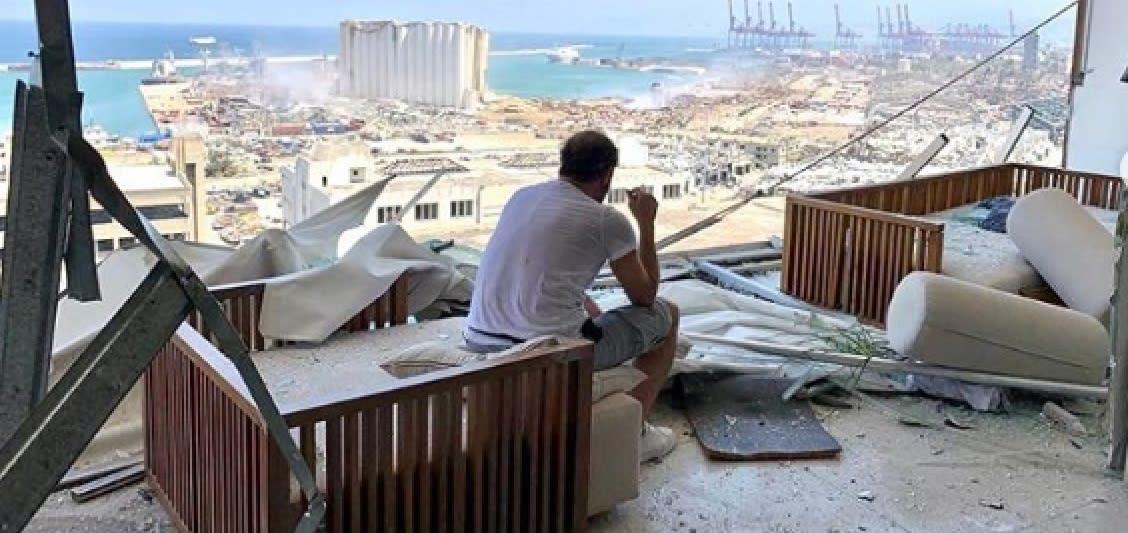 الفنان اللبناني عادل كرم يجلس وسط حطام منزله في أعقاب انفجار مرفأ بيروت الذي تبدو آثاره في الصورة