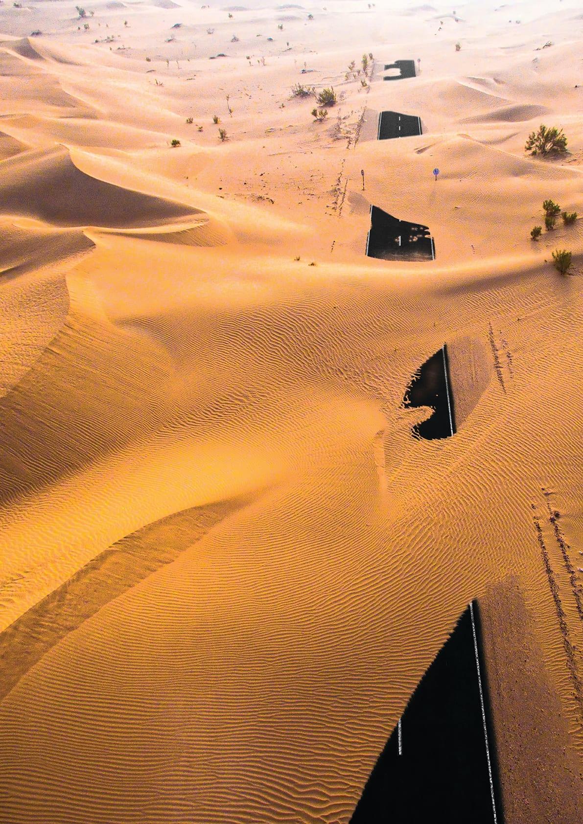 طريق مهجور تغطيه رمال صحراء أبوظبي