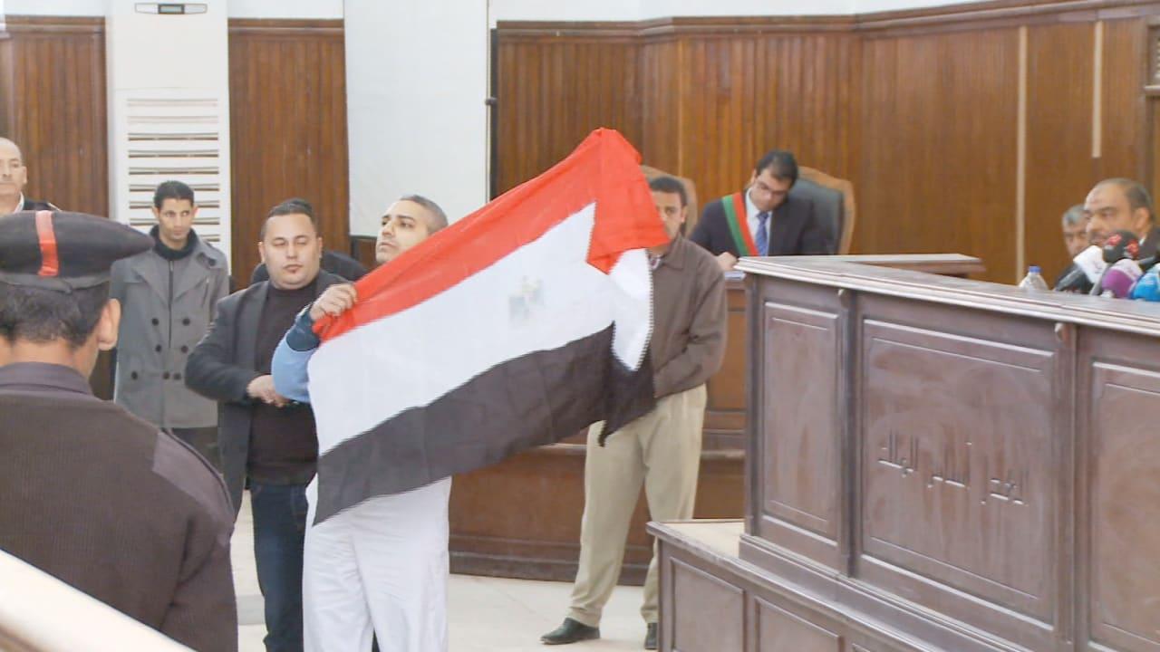 بالفيديو.. أحد صحفيي الجزيرة يرفع علم مصر أمام المحكمة