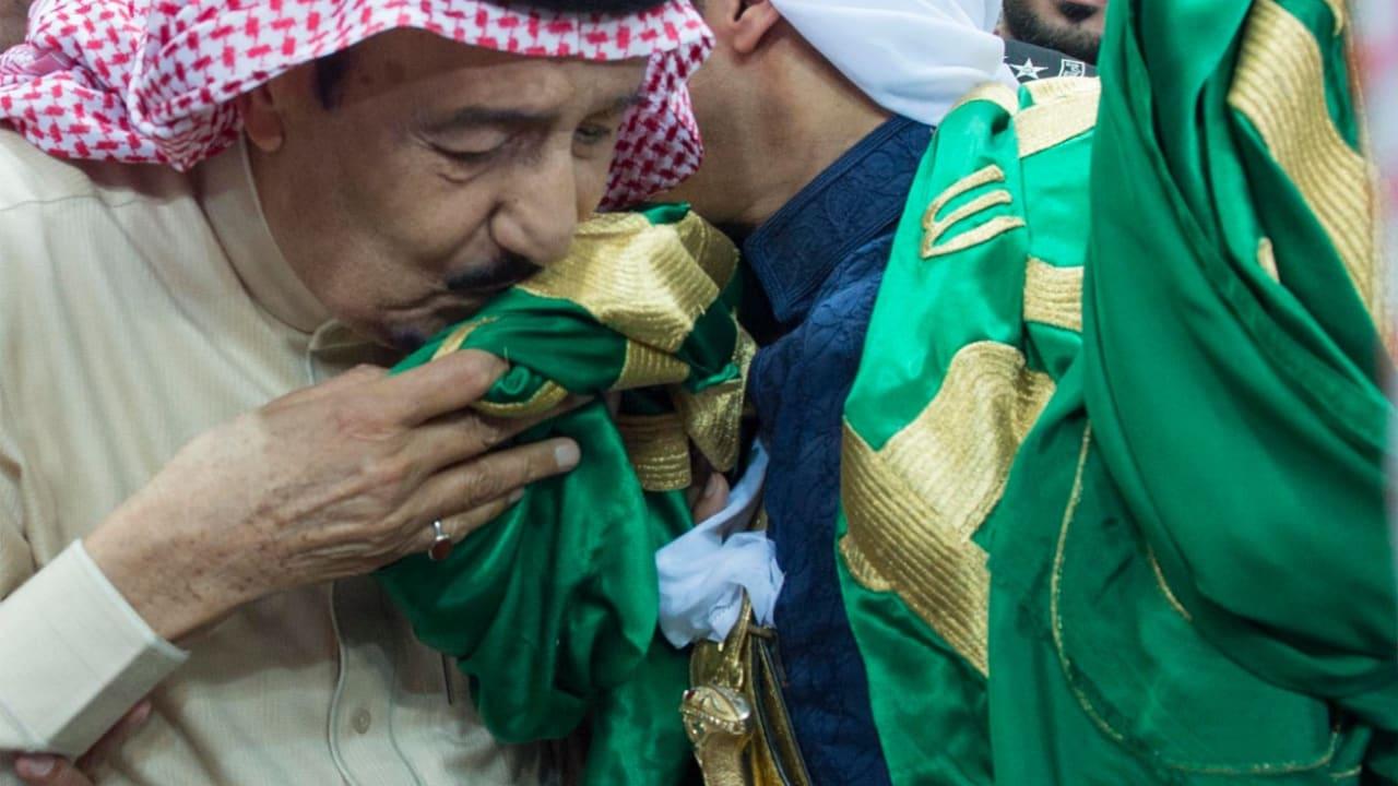"""بالصور: الملك سلمان يؤدي """"العرضة"""" بالسيف ويقبّل علم السعودية.. ونجله الأمير محمد يزور جرحى الجيش بجازان"""