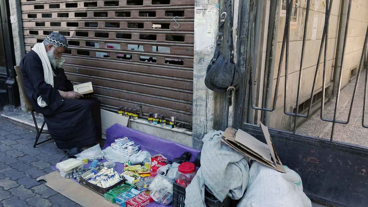 مسن يفترش الأرض ليعرض بعضا من الأغراض ليبيعها في دمشق.