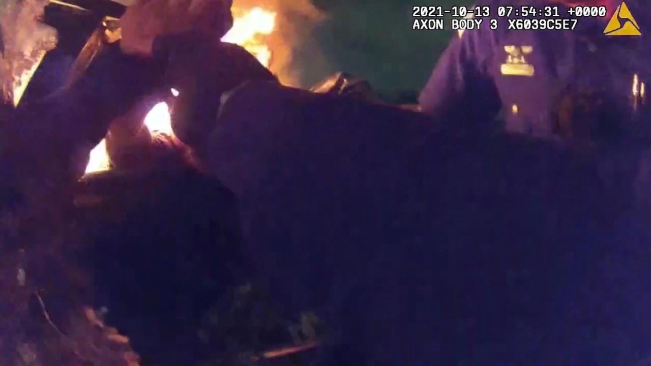 شاهد لحظات الخوف خلال إنقاذ ضابطي شرطة لرجل فاقد الوعي بسيارة تلتهمها النيران