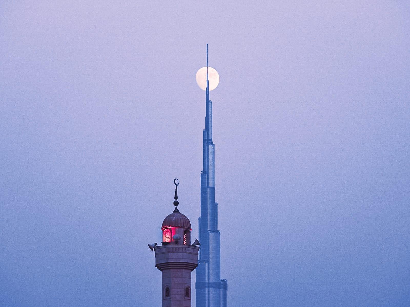 في دبي..شاهد القمر يلامس قمة أعلى برج في العالم