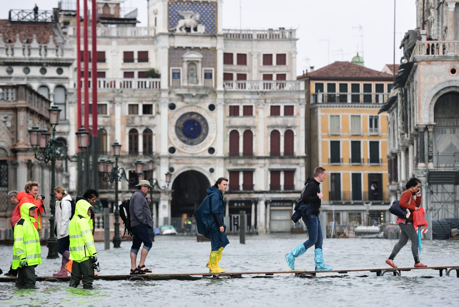 أشخاص يعبرون ساحة سان مارك التي غمرتها المياه على ممشى مرتفع