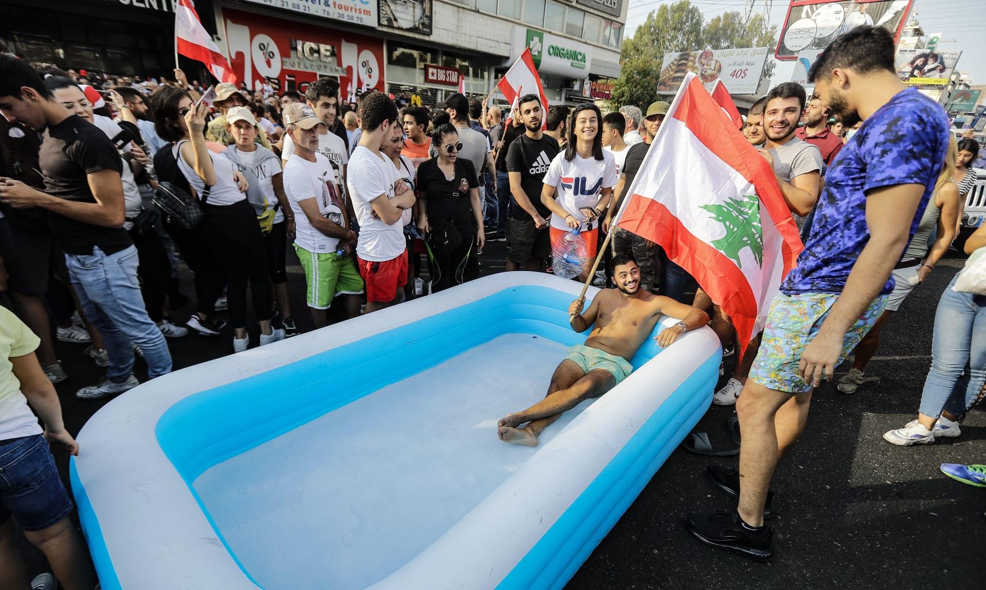 متظاهر لبناني يحمل العلم ويجلس في بركة على طريق سريع يربط بيروت بشمال لبنان