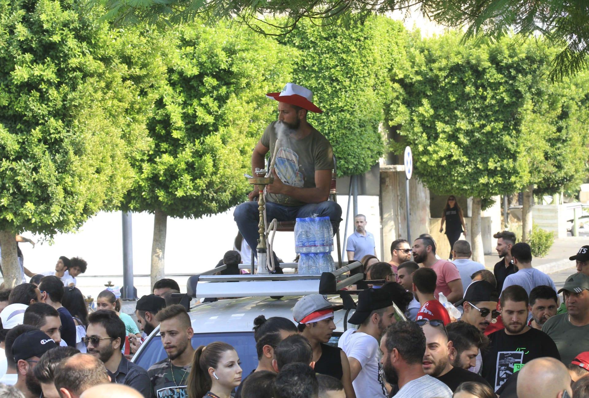 شاب يدخن النرجيلة في صيدا أثناء الاحتجاجات التي تشهدها البلاد
