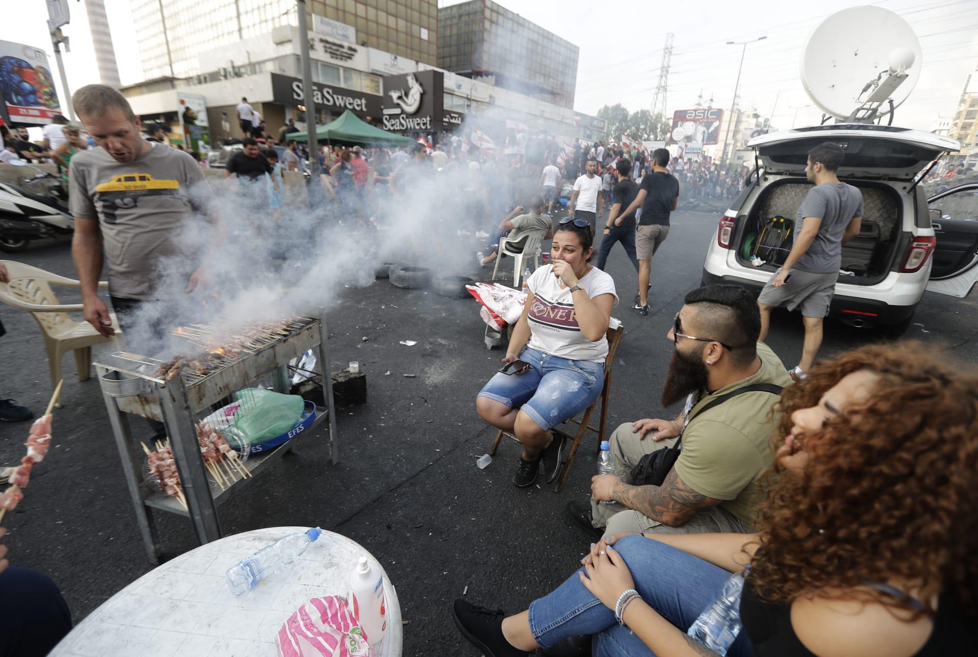 متظاهر لبناني يشوي اللحم على طريق سريع يربط بيروت بشمال لبنان، في زوق مصبح