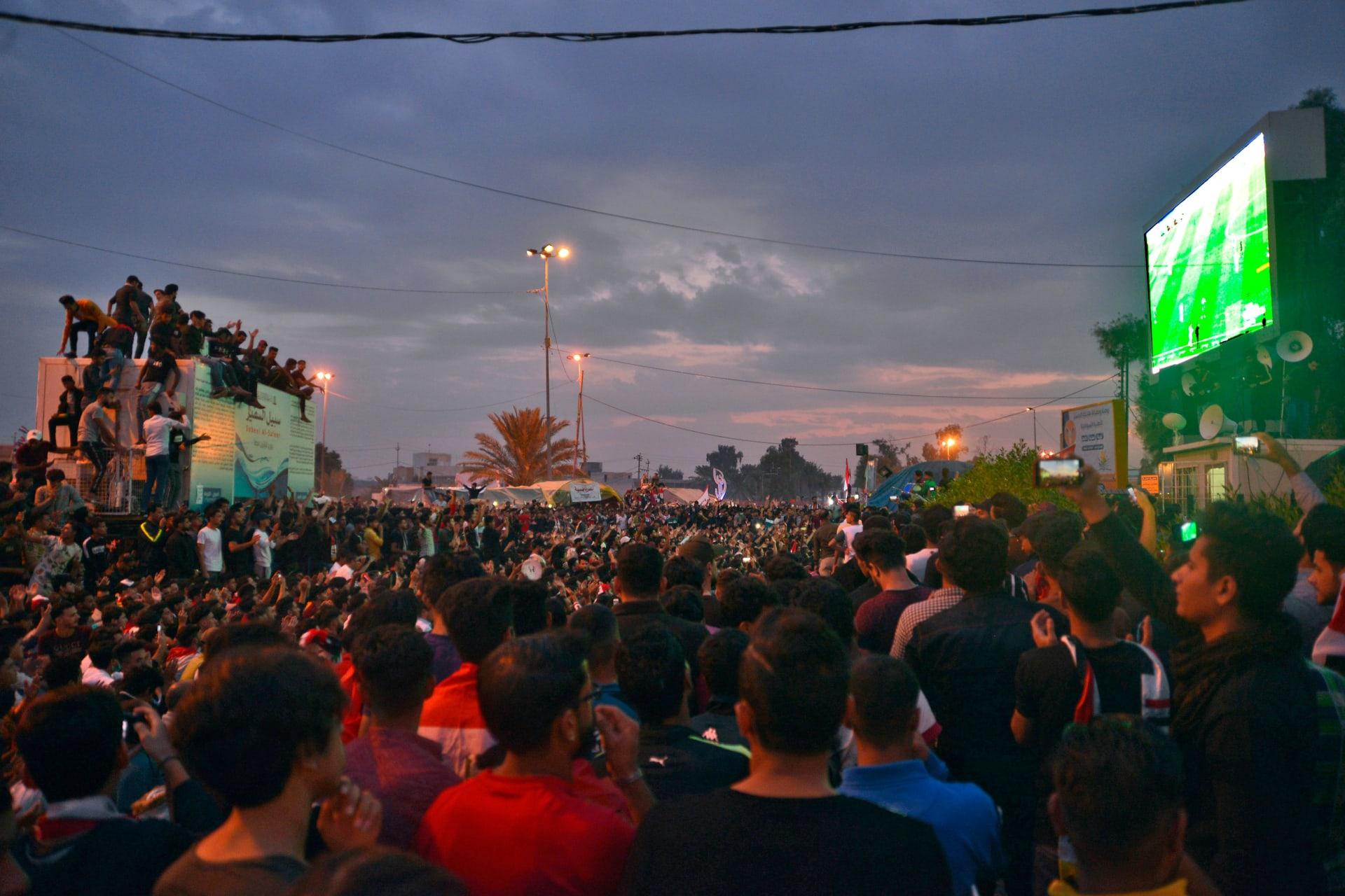 آلاف المحتجين بساحة التحرير في بغداد يتابعون مباراة منتخب بلادهم مع المنتخب الإيراني