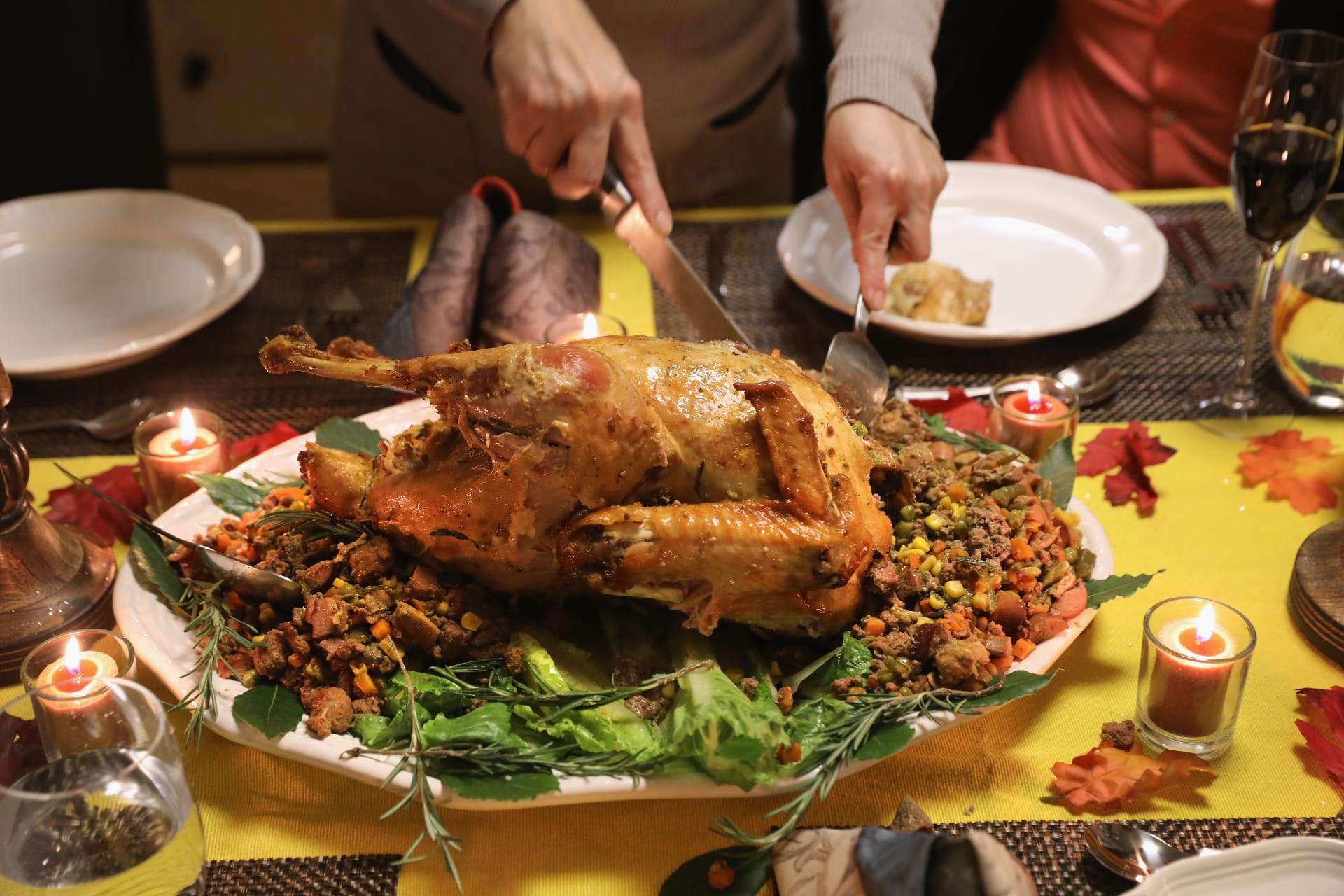 مواطنون أمريكيون يحتفلون بعيد الشكر ويتناولون طبق الديك الرومي الى جانب أطباق أخرى