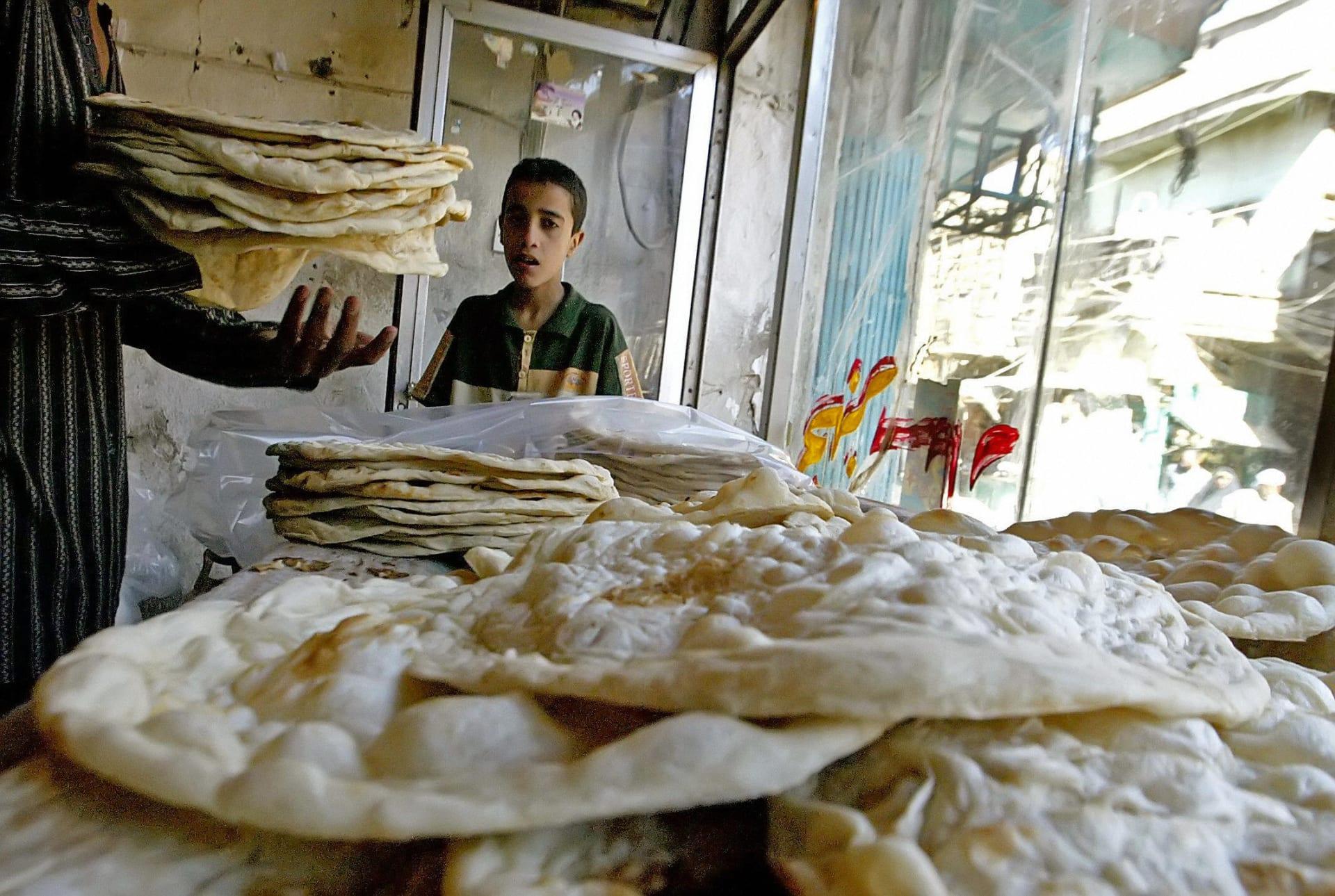 طفل يشتري الخبز من أحد المخابز المحلية بالعراق