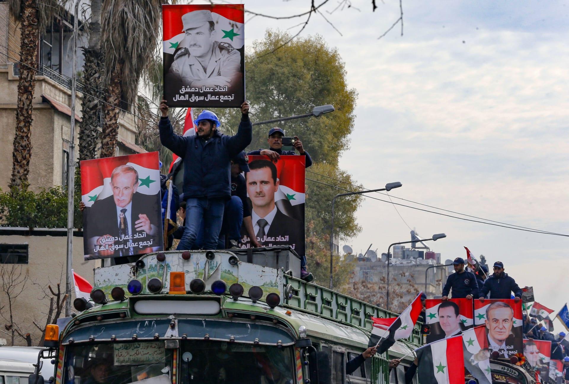 عمال يحملون صورًا للرئيس السوري بشار الأسد ووالده حافظ الاسد في وسط دمشق