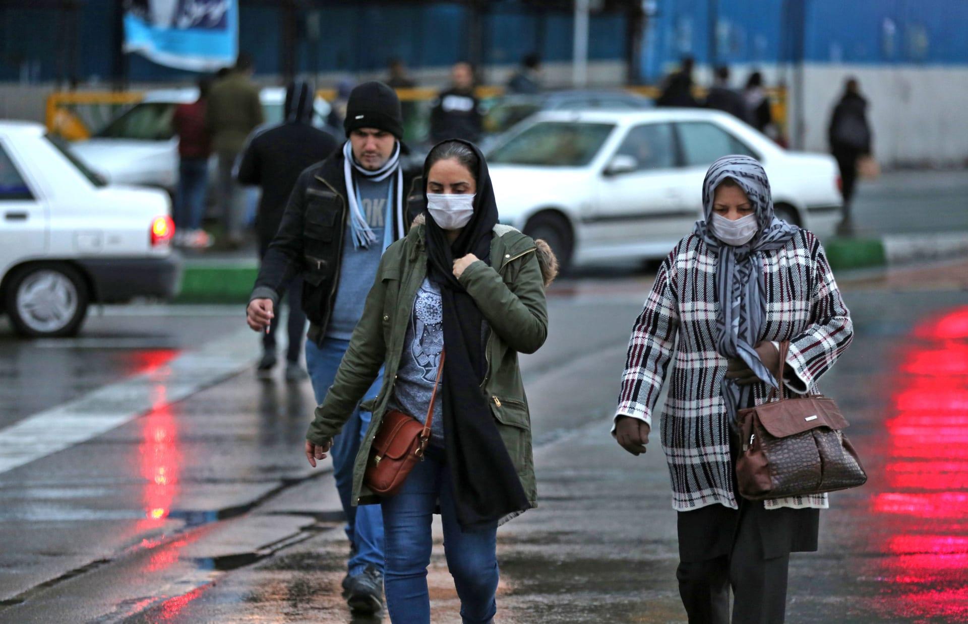 سيدتان إيرانيتان ترتديان قناع طبي واقي بعد اكتشاف حالات إصابة بفيروس كورونا في البلاد