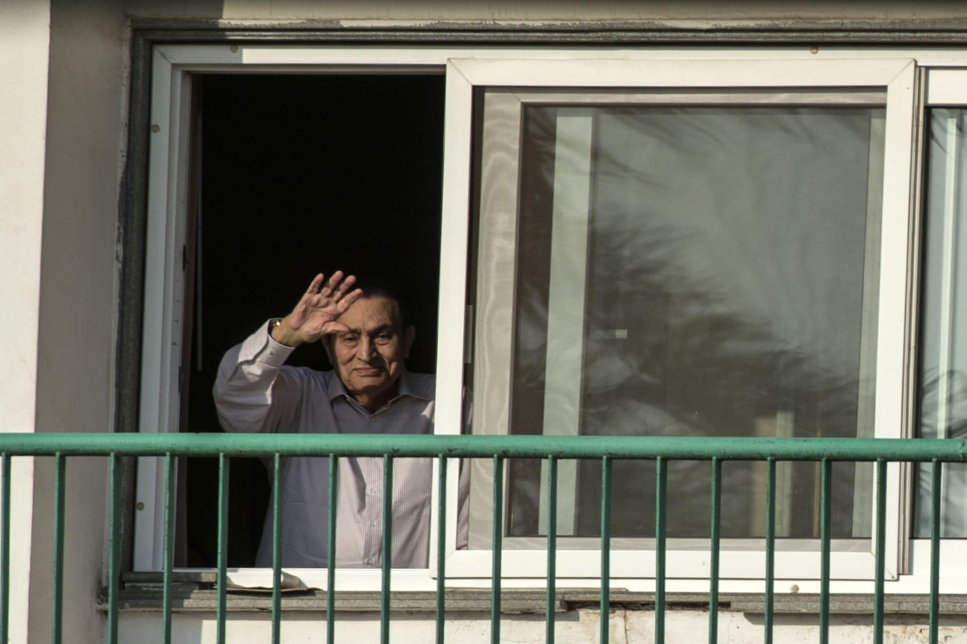 الرئيس المصري الأسبق حسني مبارك يلوح لمؤيديه من غرفته في مستفى المعادي العسكري بالقاهرة