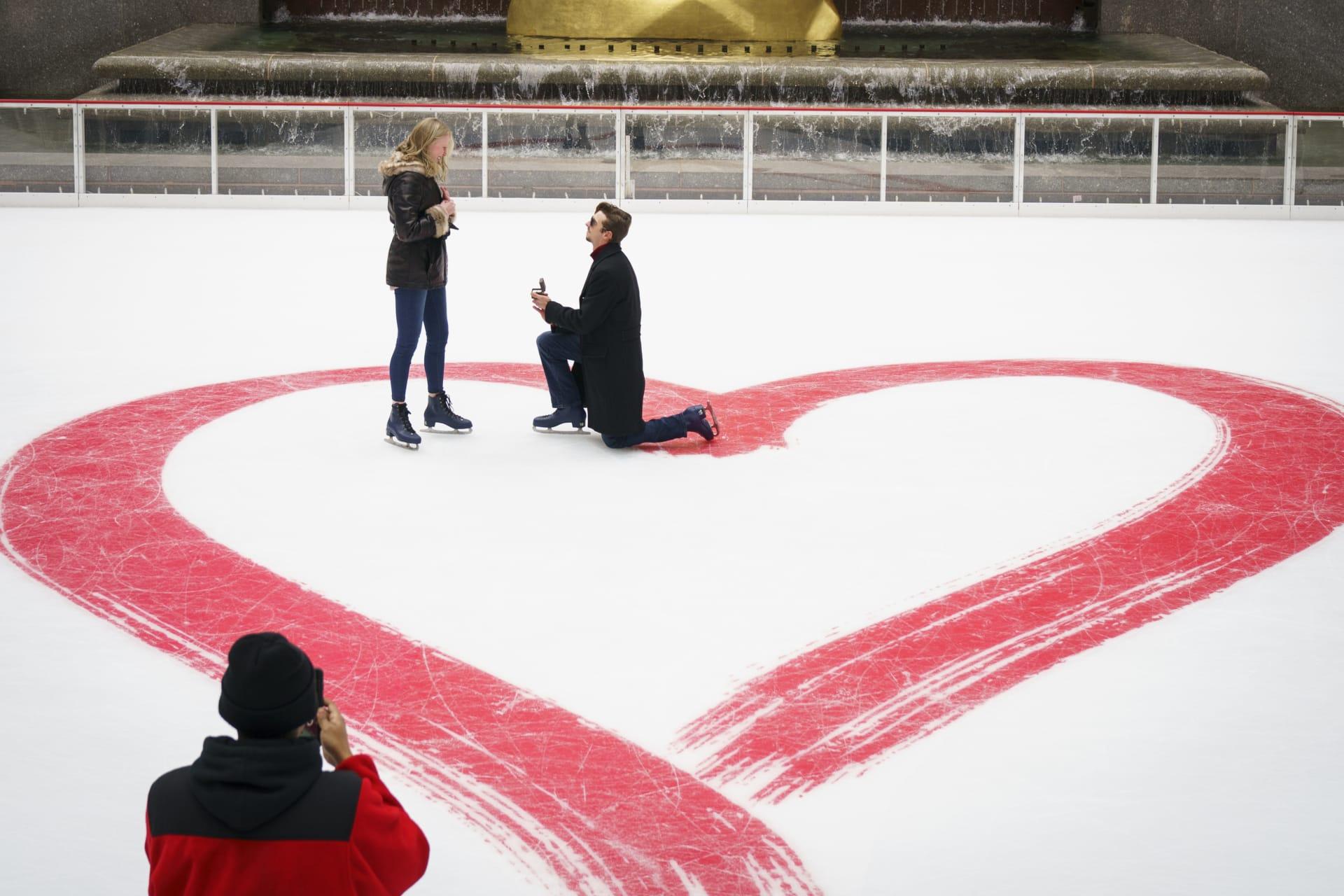 رجل يتقدم لفتاة في يوم عيد الحب في مركز للتزلج على الجليد في نيويورك