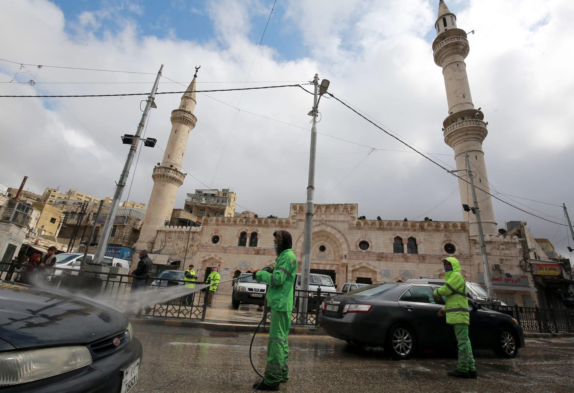 عمال يقومون بتعقيم السيارات في العاصمة الأردنية عمان بعد انتشار فيروس كورونا المستجد