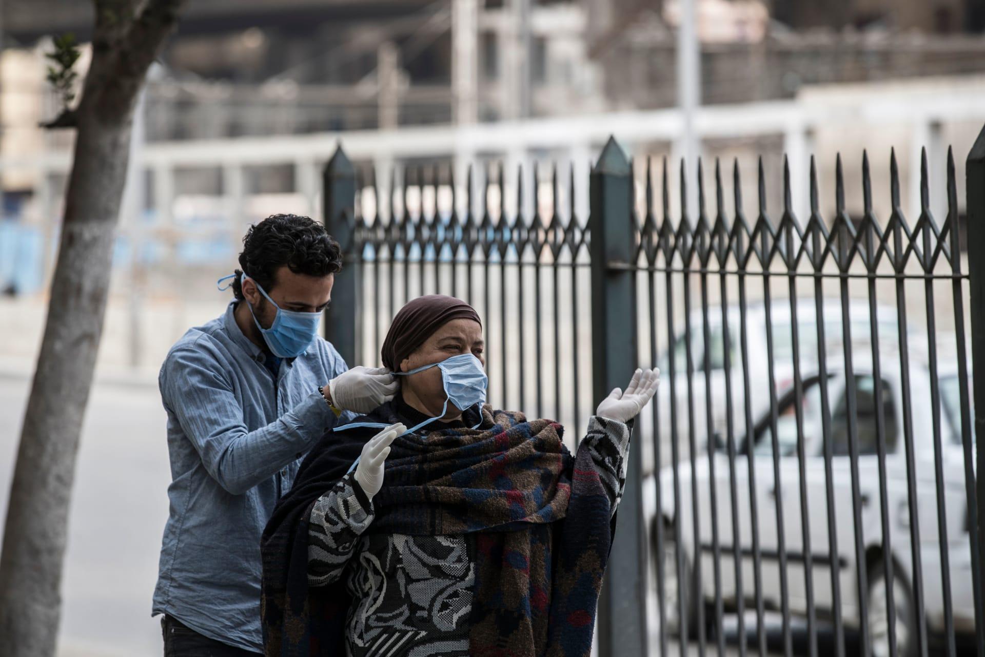 متطوع يربط قناعا لإمرأة مصرية في شارع بالعاصمة المصرية القاهرة