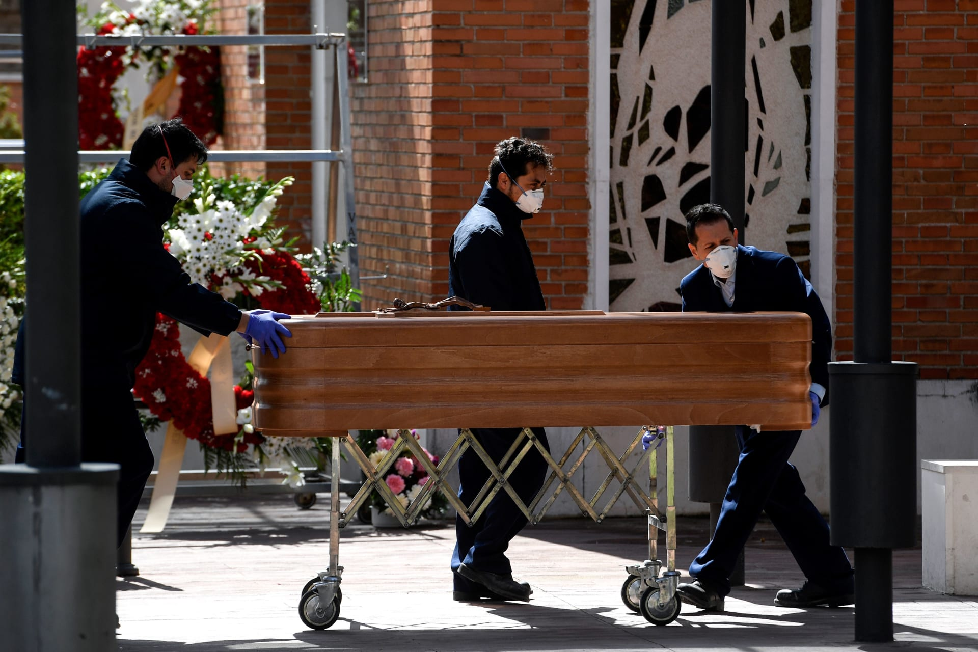 عمال يحملون جثمان أحد ضحايا فيروس كورونا المستجد في إسبانيا