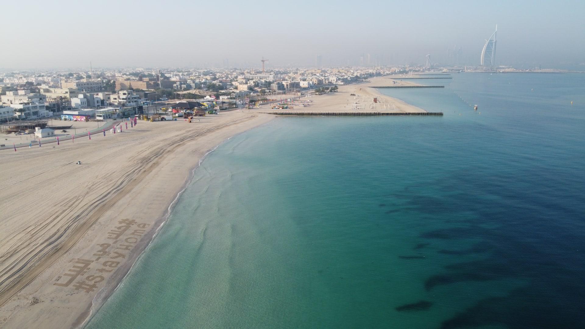"""عبارة """"خلك في البيت"""" تزين أحد شواطئ دبي"""