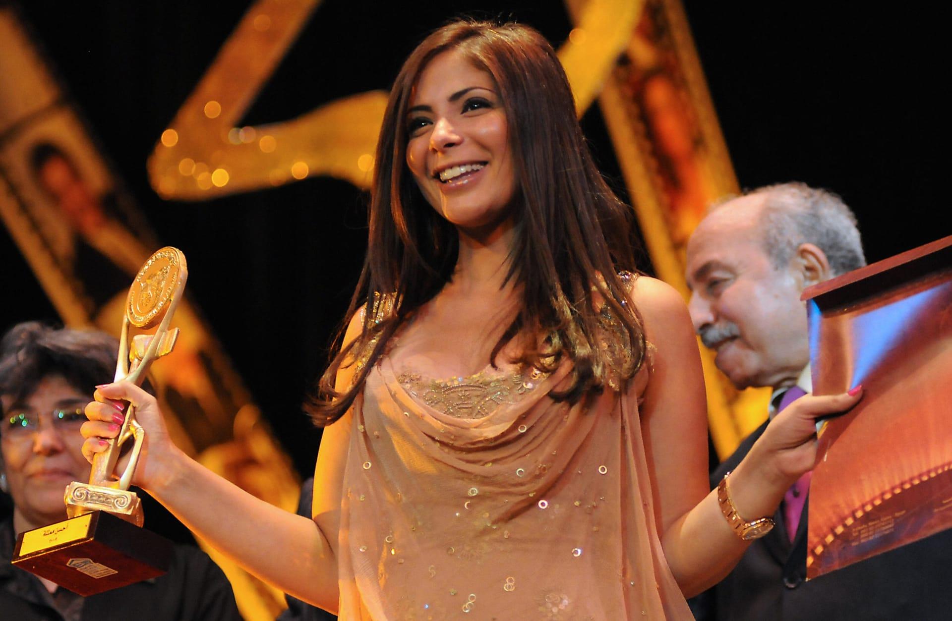 """الممثلة المصرية منى زكي تحمل جائزتها بعد فوزها بجائزة أفضل ممثلة عن دورها في """"احكي يا شهرزاد""""  في مهرجان الإسكندرية السينمائي الدولي الـ25 في 2009"""