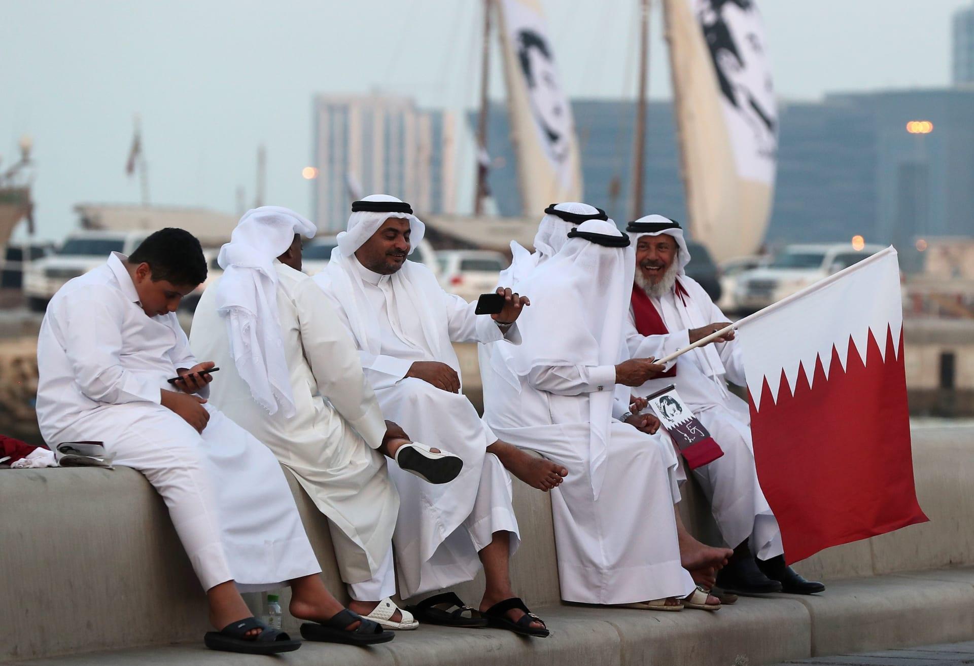 صورة أرشيفية (تعبيرية) لقطريين يرفعون أعلام بلدهم وصور الشيخ تميم في الدوحة العام 2017