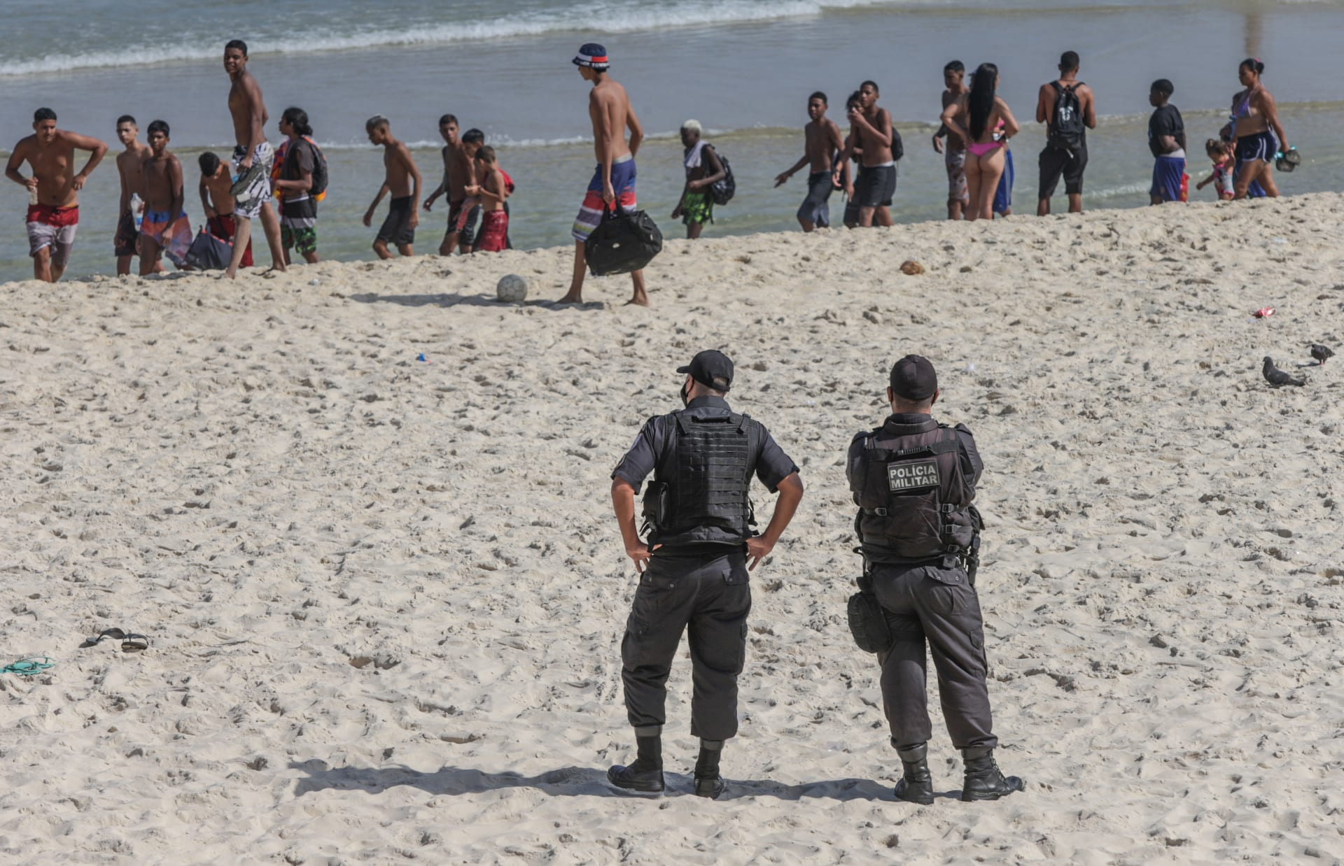 رجلا شرطة يراقبان مصطافين لدى مغادرتهم شاطىء في ريو دي جانييرو