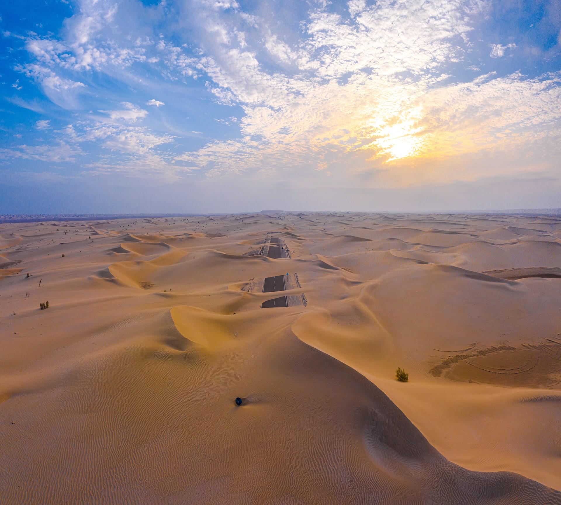 طريق مهجور غارق في بحر من رمال صحراء أبوظبي