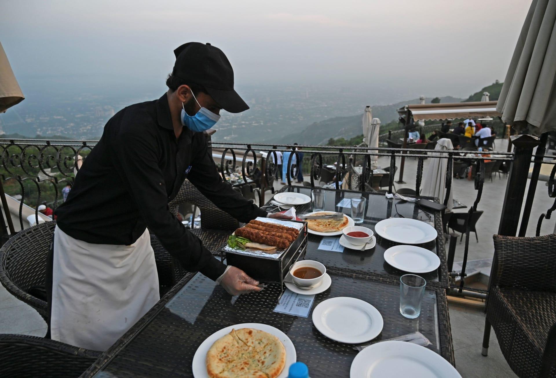 عامل باكستاني يعمل على تجهيز طاولة طعام وسط تفشي فيروس كورونا
