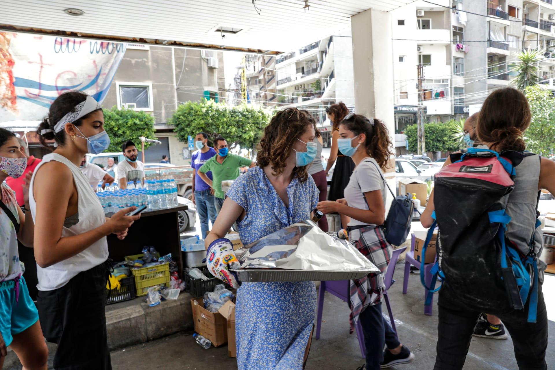 متطوعون يرتدون أقنعة واقية من فيروس كورونا خلال تقديم مساعدات للمتضررين من انفجار بيروت