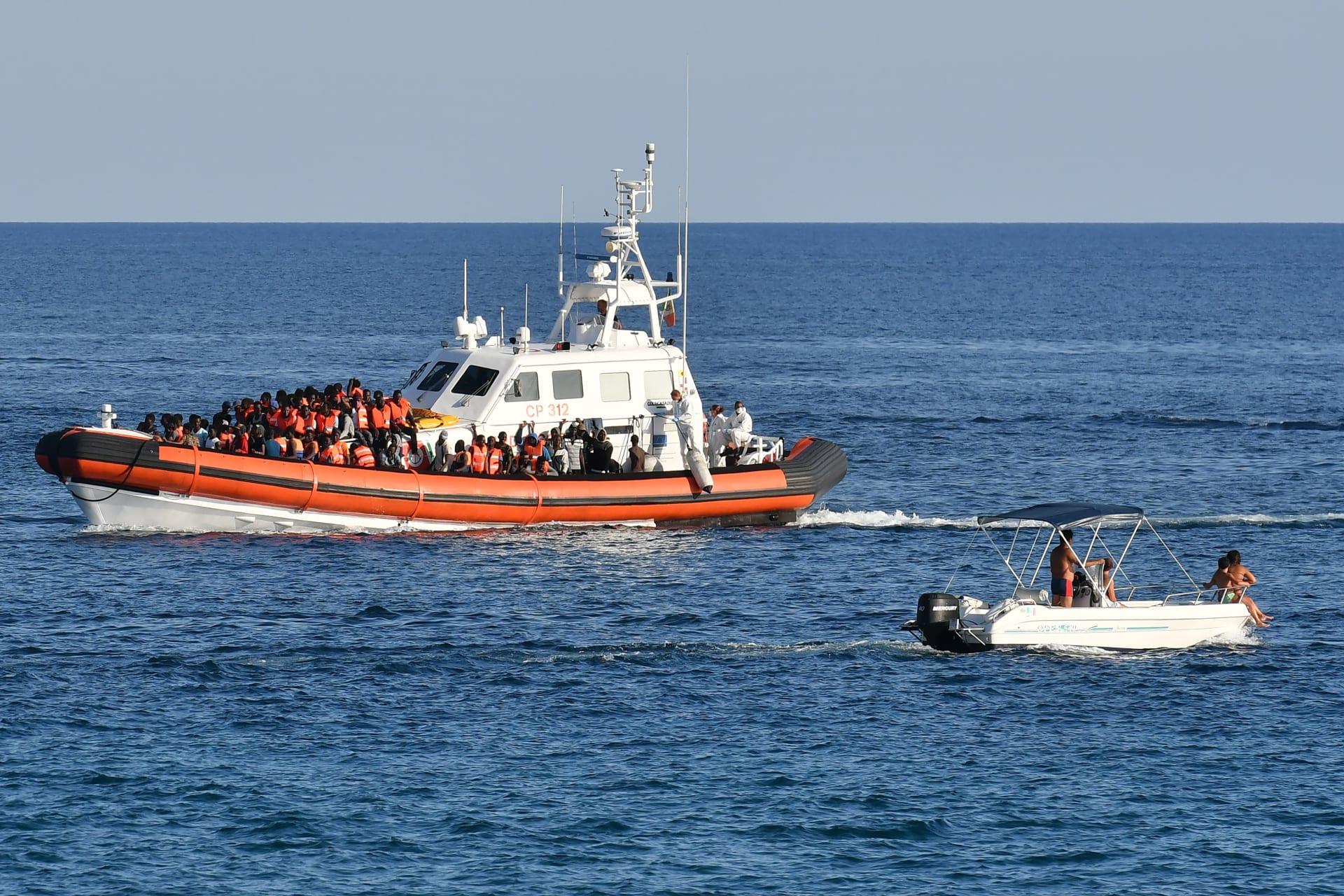 قارب لسلطات الحدود الإيطالية ينقل عددًا من المهاجرين غير الشرعيين القادمين من ليبيا
