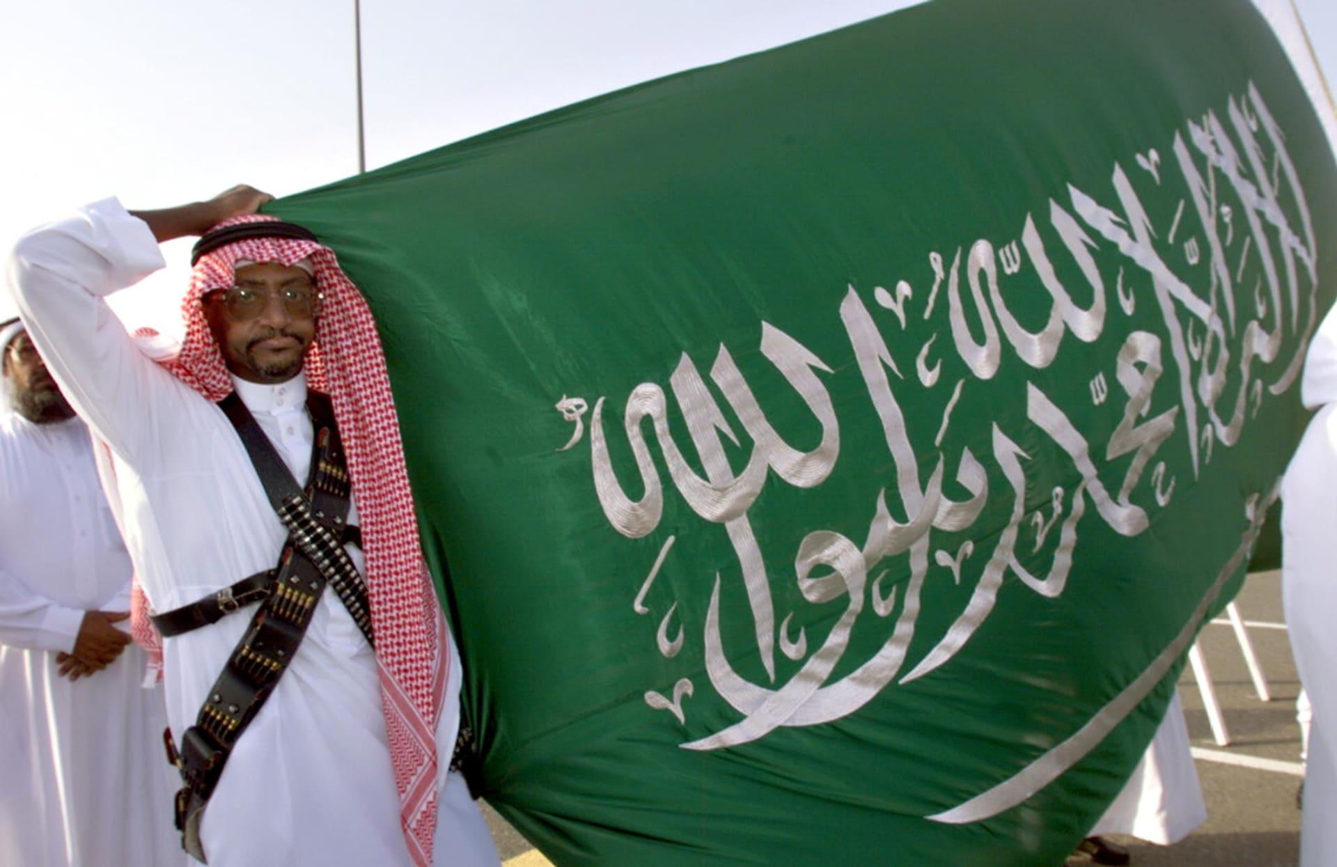 صورة أرشيفية لرجل يرفع العلم السعودي