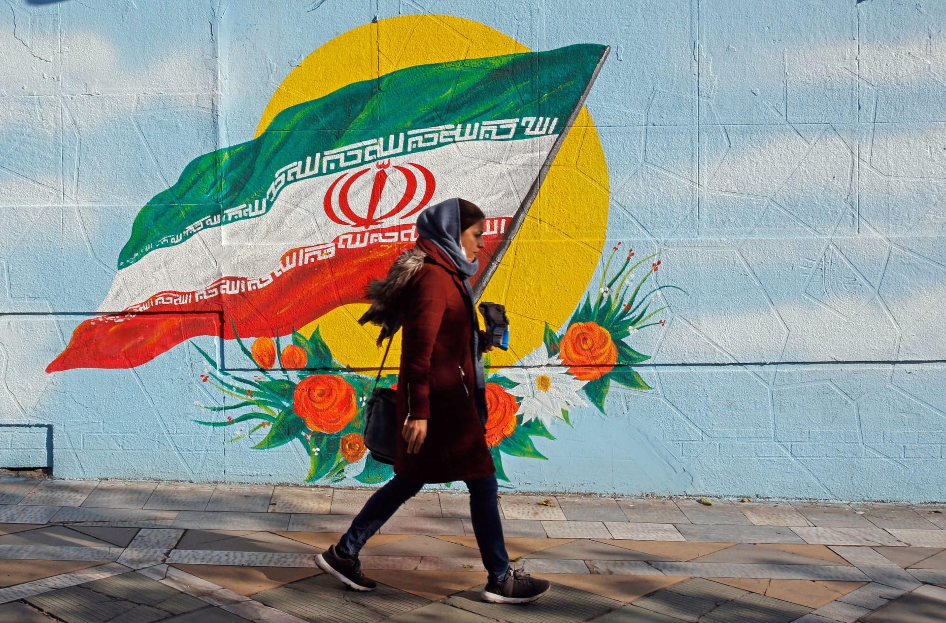 صورة أرشيفية لفتاة تسير أمام رسمة لعلم إيران في طهران