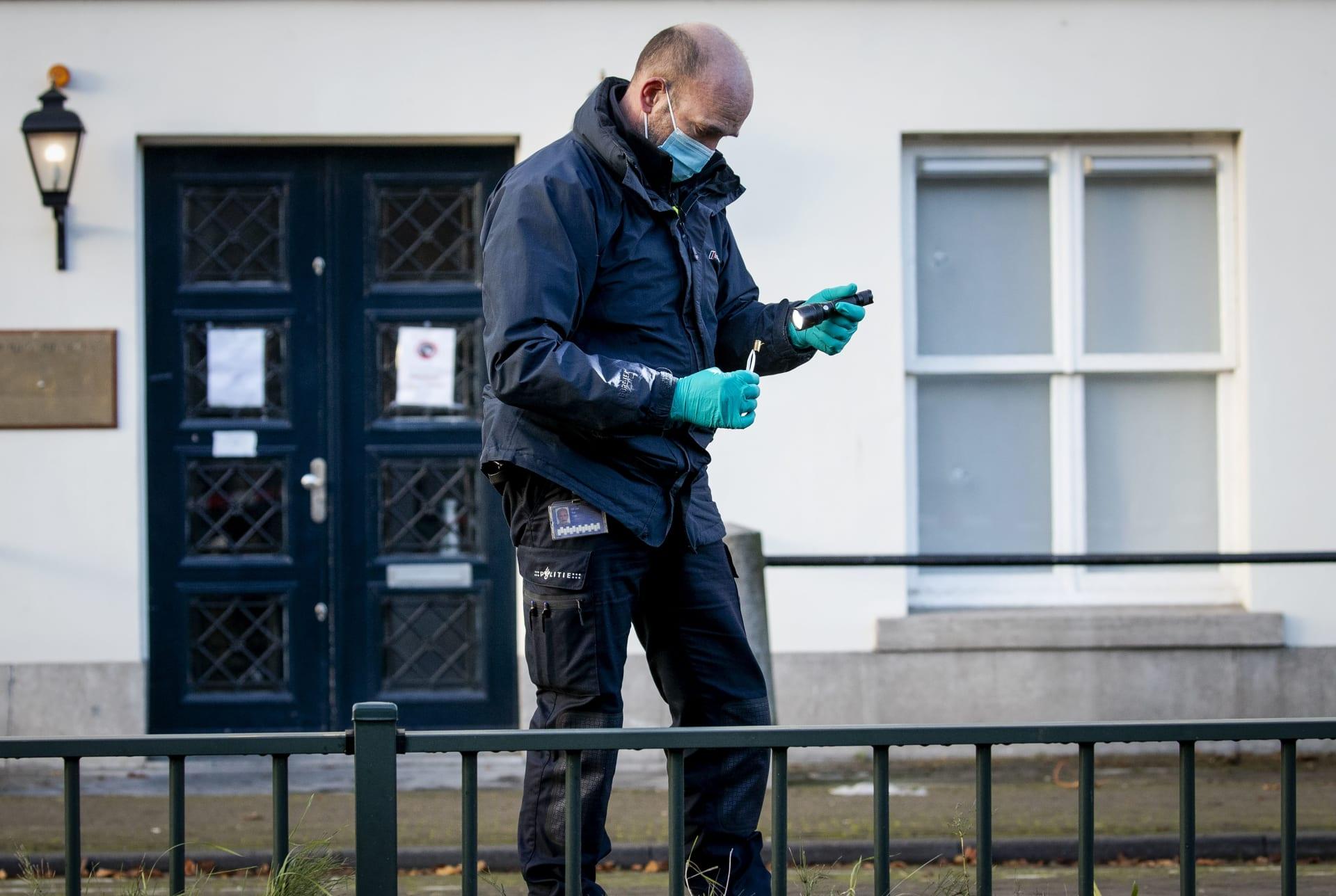 شرطي هولندي يفحص بقايا الطلقات النارية أمام السفارة السعودية