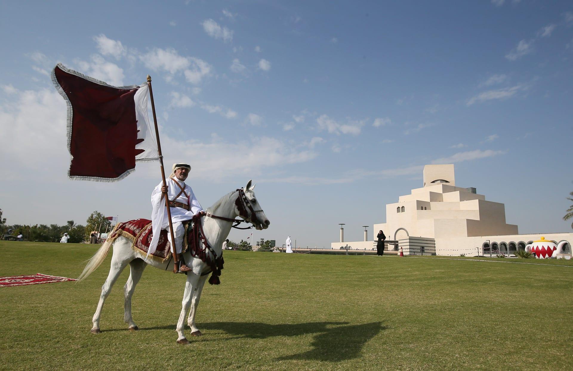 صورة ارشيفية لرجل على صهوة حصات يرفع علم قطر