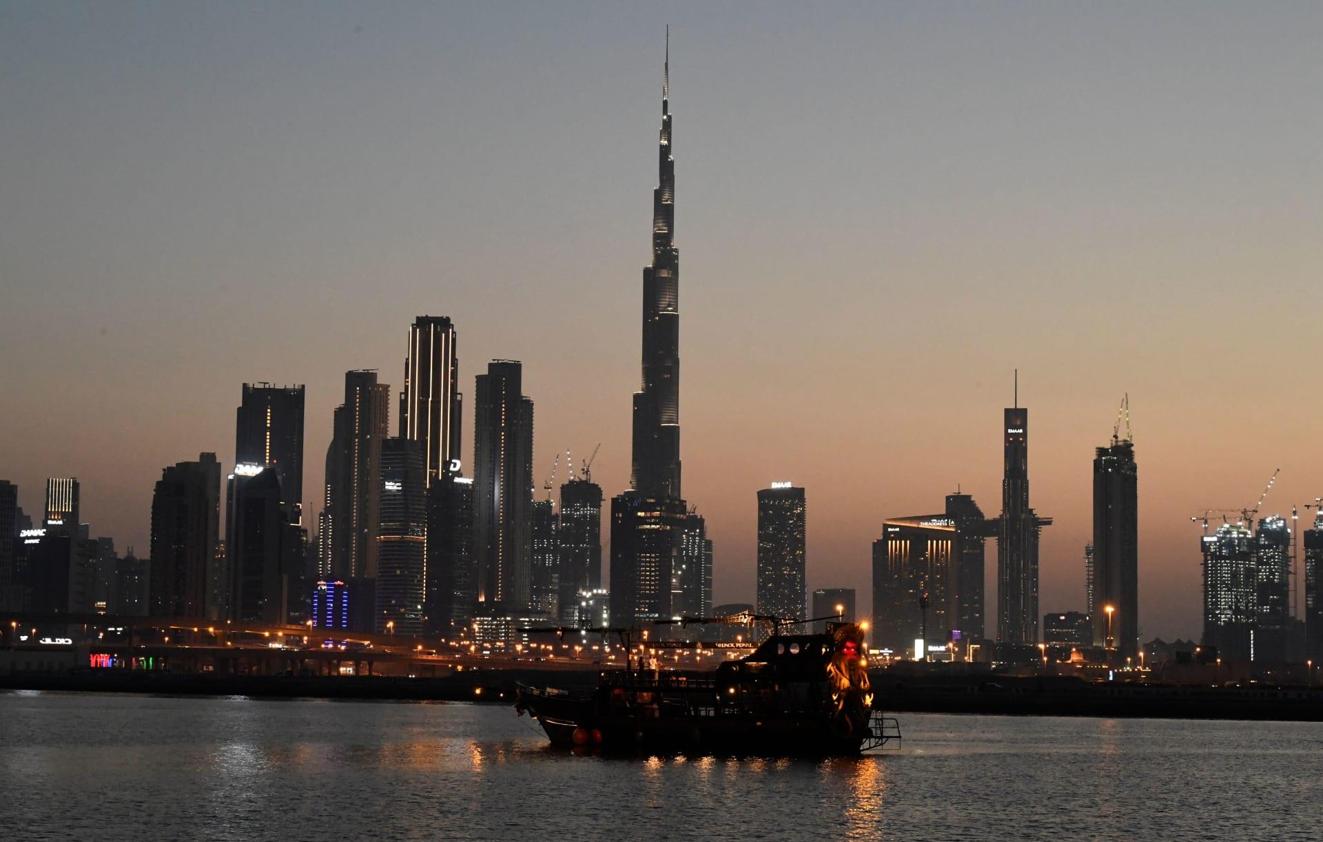 قارب يبحر عند غروب الشمس بالقرب من برج خليفة والمباني الشاهقة في مدينة دبي الإماراتية