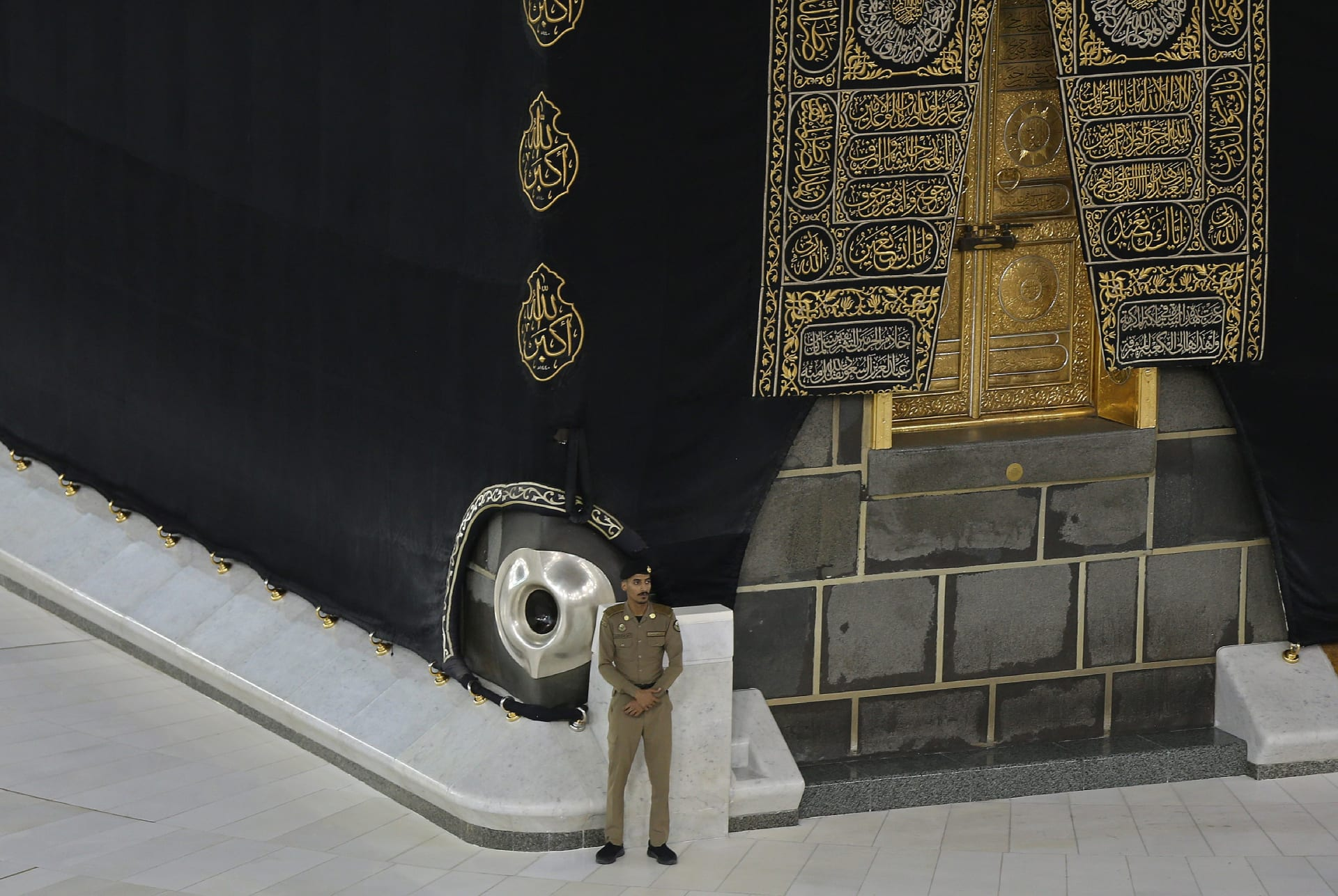صورة أرشيفية لعنصر أمن سعودي يقف إلى جانب موقع الحجر الأسود