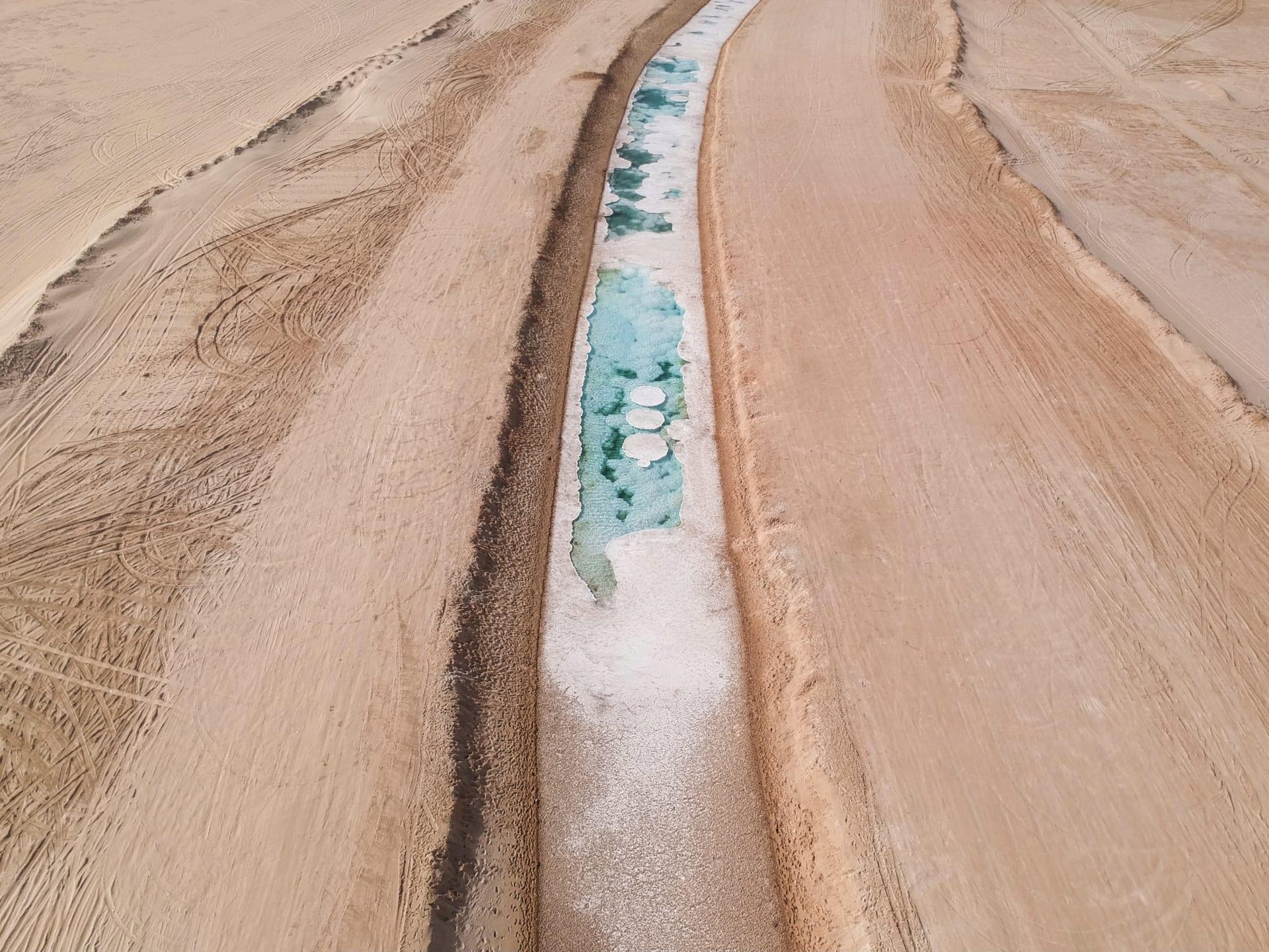 كأنها ثلوج متراكمة.. ما سر تشكل هذه البحيرة الطويلة وسط صحراء أبوظبي؟