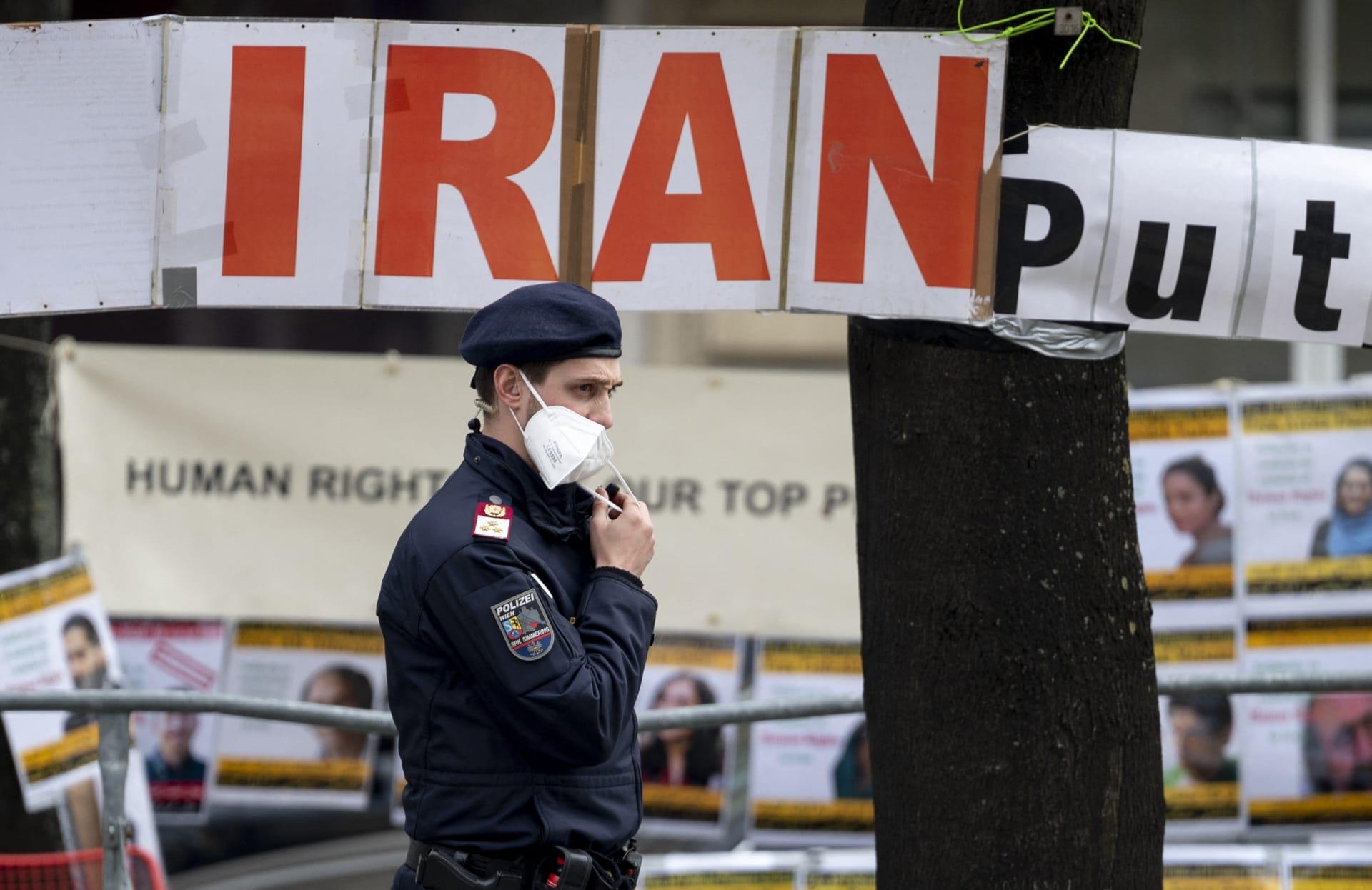 النمسا: ضابط شرطة يتوقف أمام لافتات رفعها أعضاء في المجلس الوطني للمقاومة الإيرانية، وهي جماعة إيرانية معارضة، أمام فندق غراند فيينا خلال المحادثات النووية المغلقة مع إيران في 27 أبريل/نيسان 2021