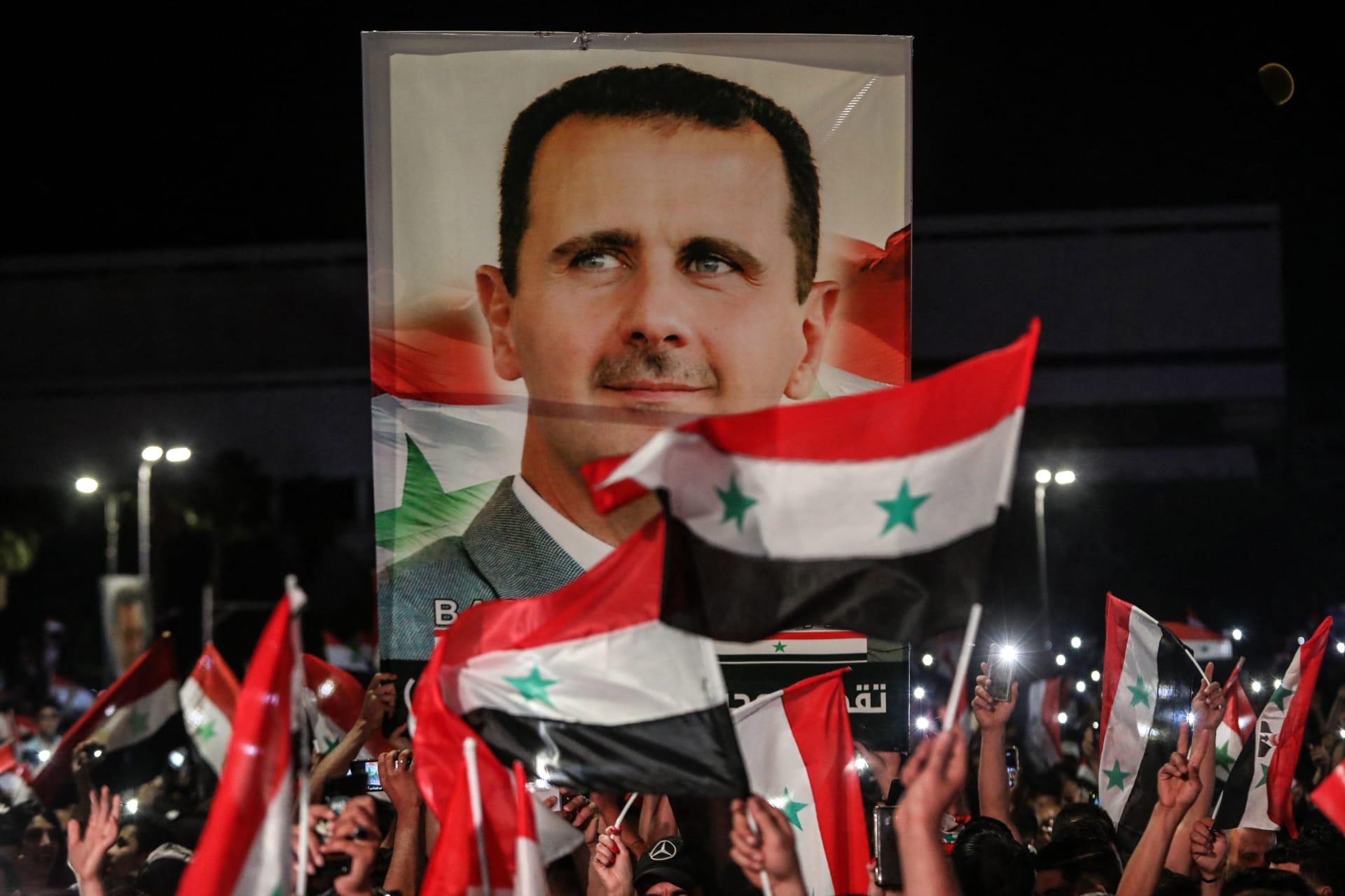 سوريون يلوحون بالأعلام الوطنية ويحملون صورة كبيرة بلرئيس بشار الأسد وهم يحتفلون في شوارع العاصمة دمشق، بعد يوم من الانتخابات