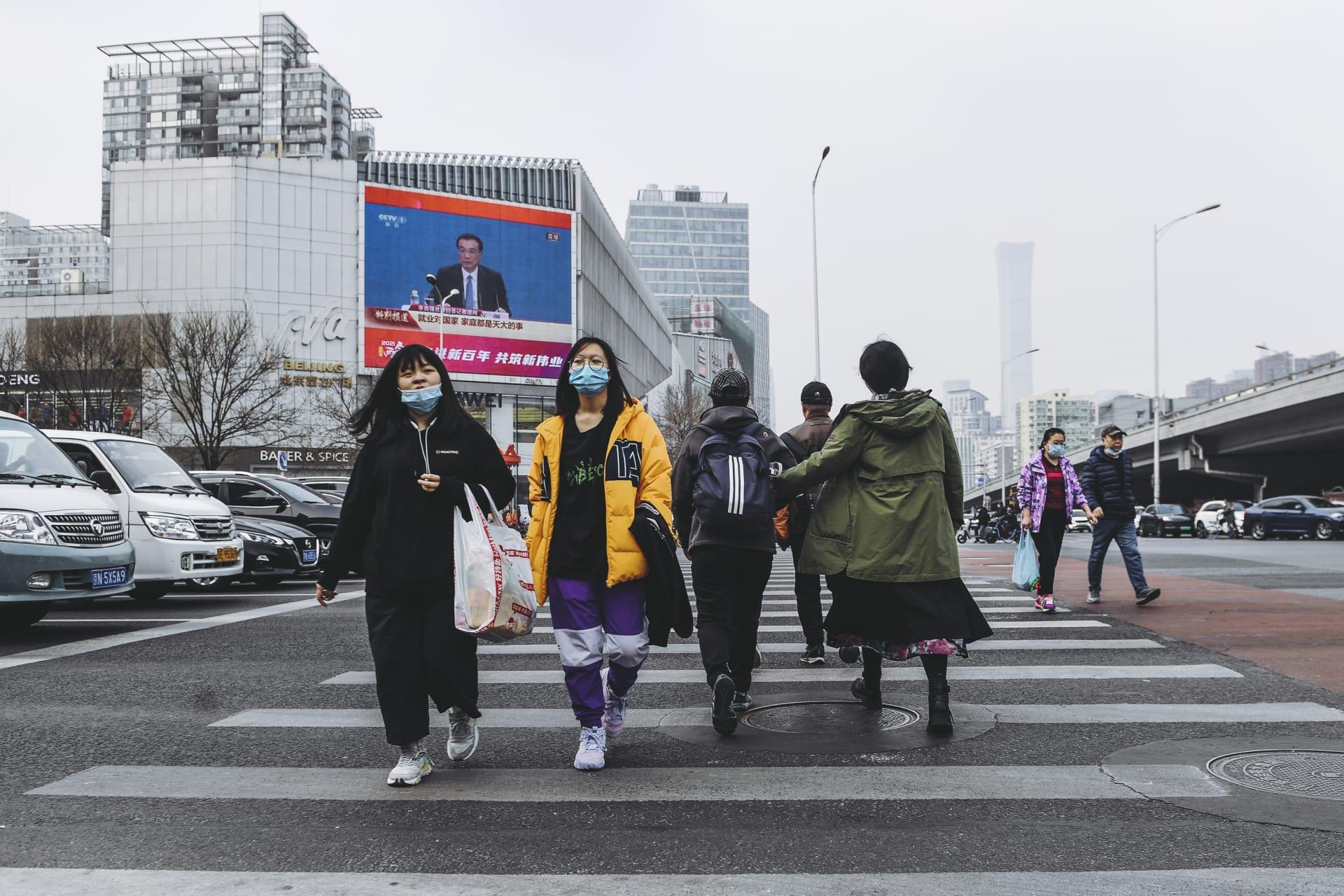 الناس يسيرون على مفترق طرق أثناء بث مباشر على شاشة كبيرة تقارير عن إغلاق المؤتمر الوطني لنواب الشعب الصيني في بكين في 11 مارس 2021 في بكين