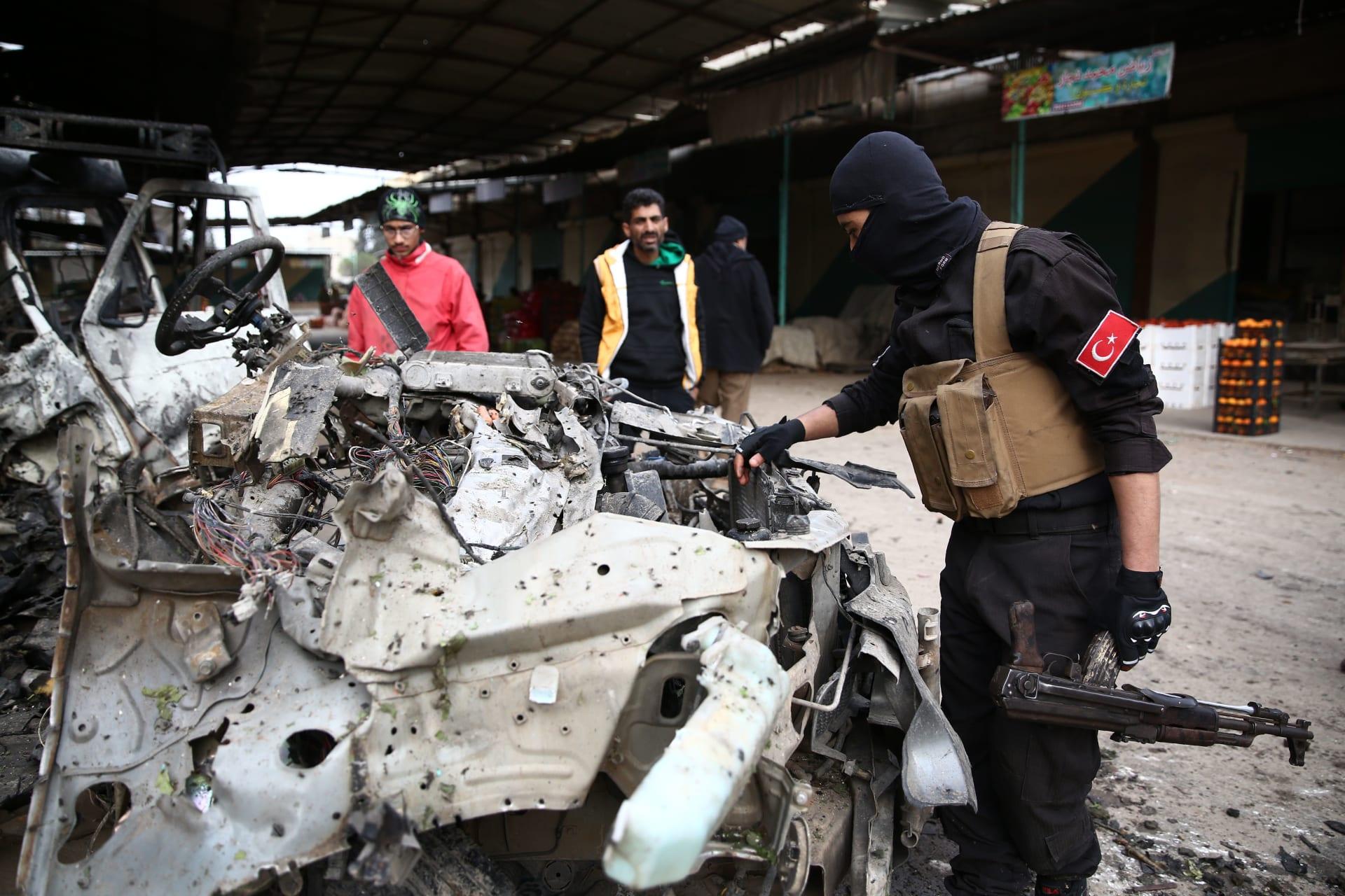 مقاتل سوري موالي لتركيا يتفقد بقايا سيارة انفجرت في سوق في مدينة عفرين شمال سوريا، في 16 ديسمبر 2018.