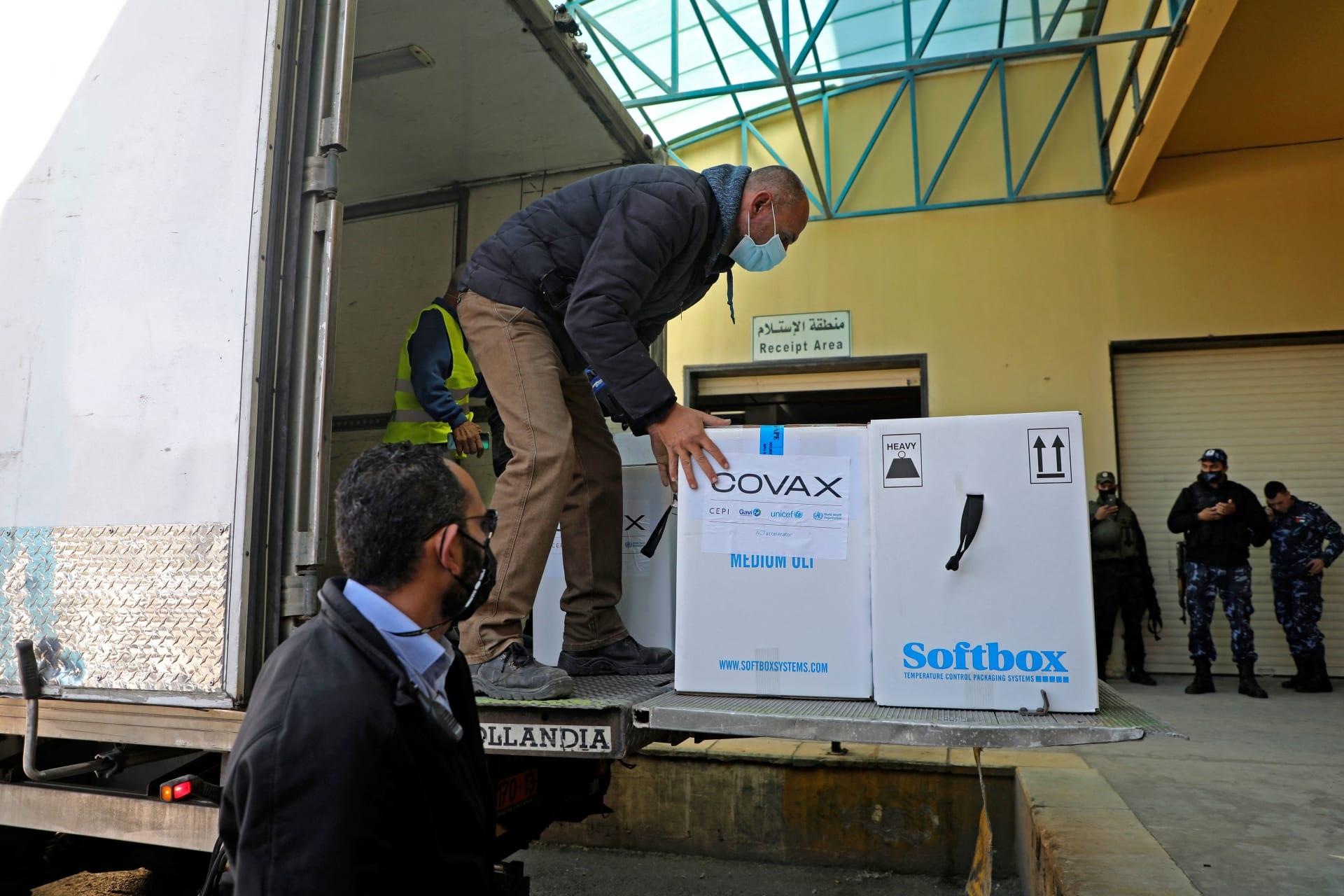 عامل يفرغ شاحنة مبردة تحمل أول شحنة من لقاح كورونا عبر برنامج Covax التابع للأمم المتحدة، في مدينة نابلس بالضفة الغربية ، 17 مارس 2021