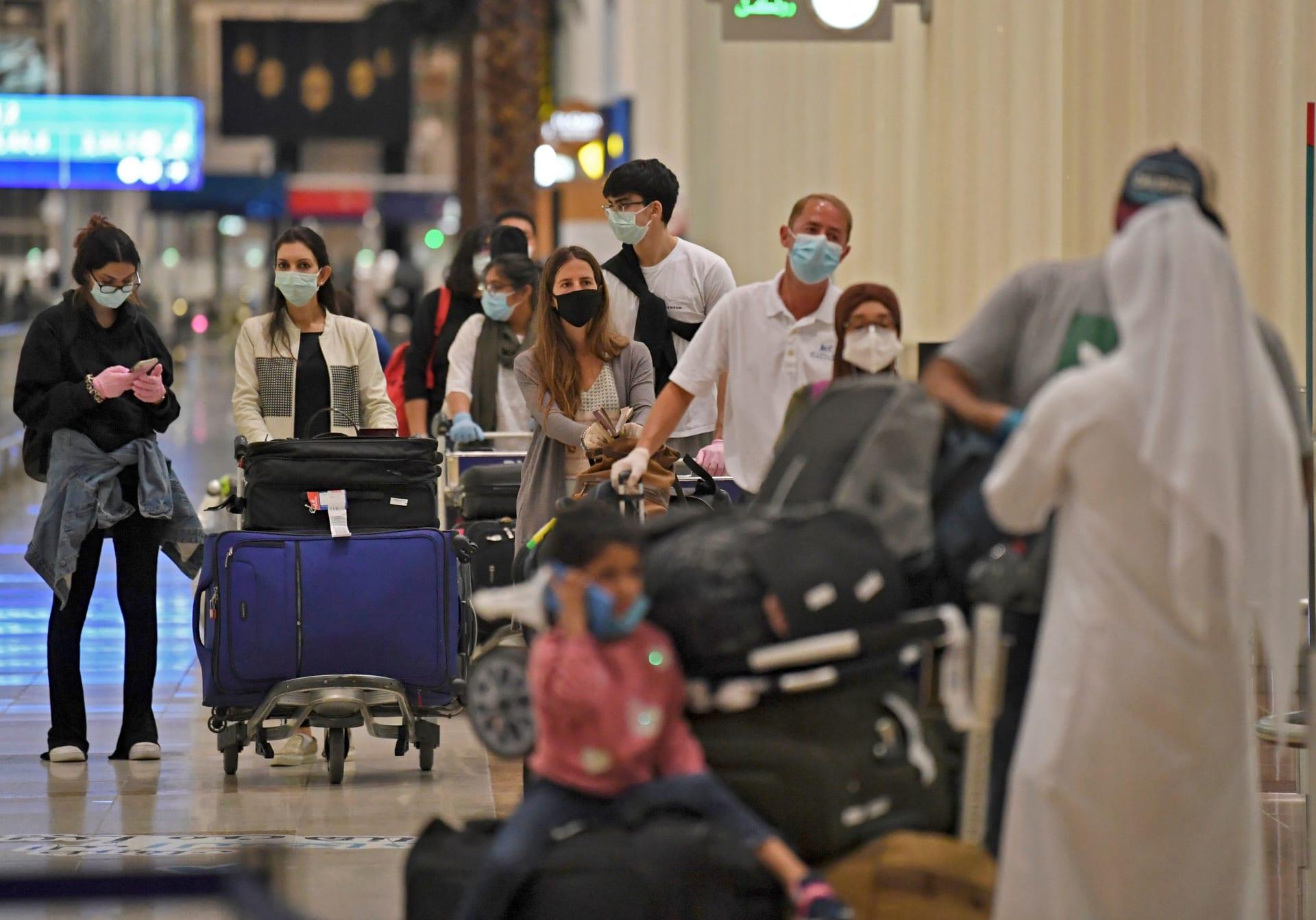 يصطف ركاب رحلة طيران الإمارات من لندن قبل أن يتم فحصهم من قبل العاملين الصحيين في مطار دبي الدولي في 8 مايو 2020