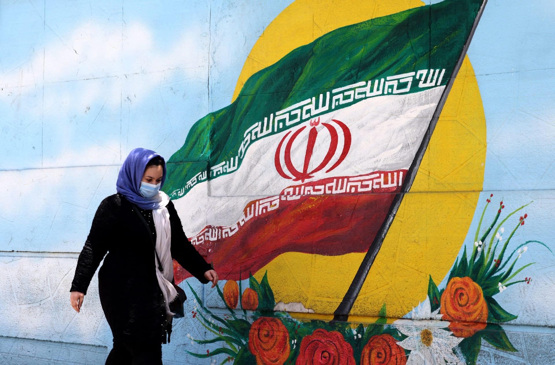 صورة أرشيفية لمرأة تمر قرب رسمة للعلم الإيراني في ظهران