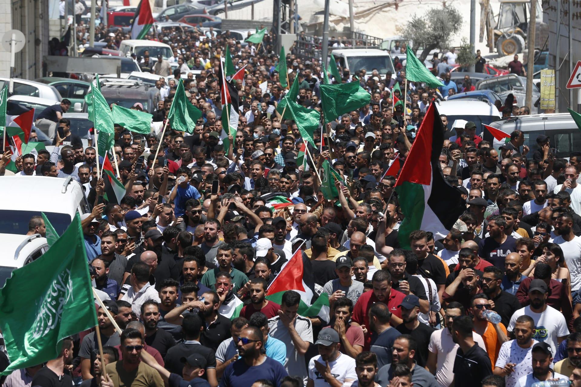 مشيعون يسيرون في موكب جنائزي مع جثمان الناشط الحقوقي والناقد للسلطة الفلسطينية نزار بنات ، الذي توفي بعد وقت قصير من اعتقاله في اليوم السابق ، في الخليل بالضفة الغربية المحتلة في 25 يونيو 2021