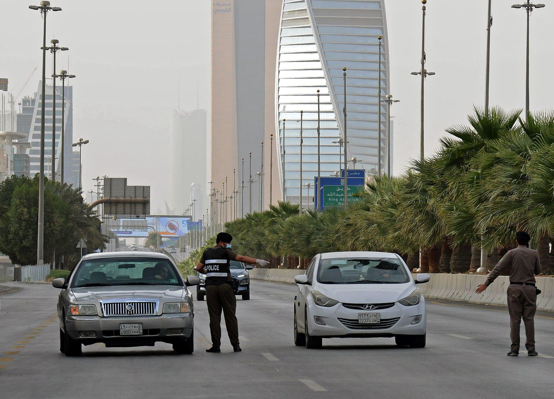 صورة التقطت في 26 مارس 2020، تظهر رجال شرطة سعوديين يحرسون نقطة تفتيش على طريق الملك فهد في العاصمة الرياض