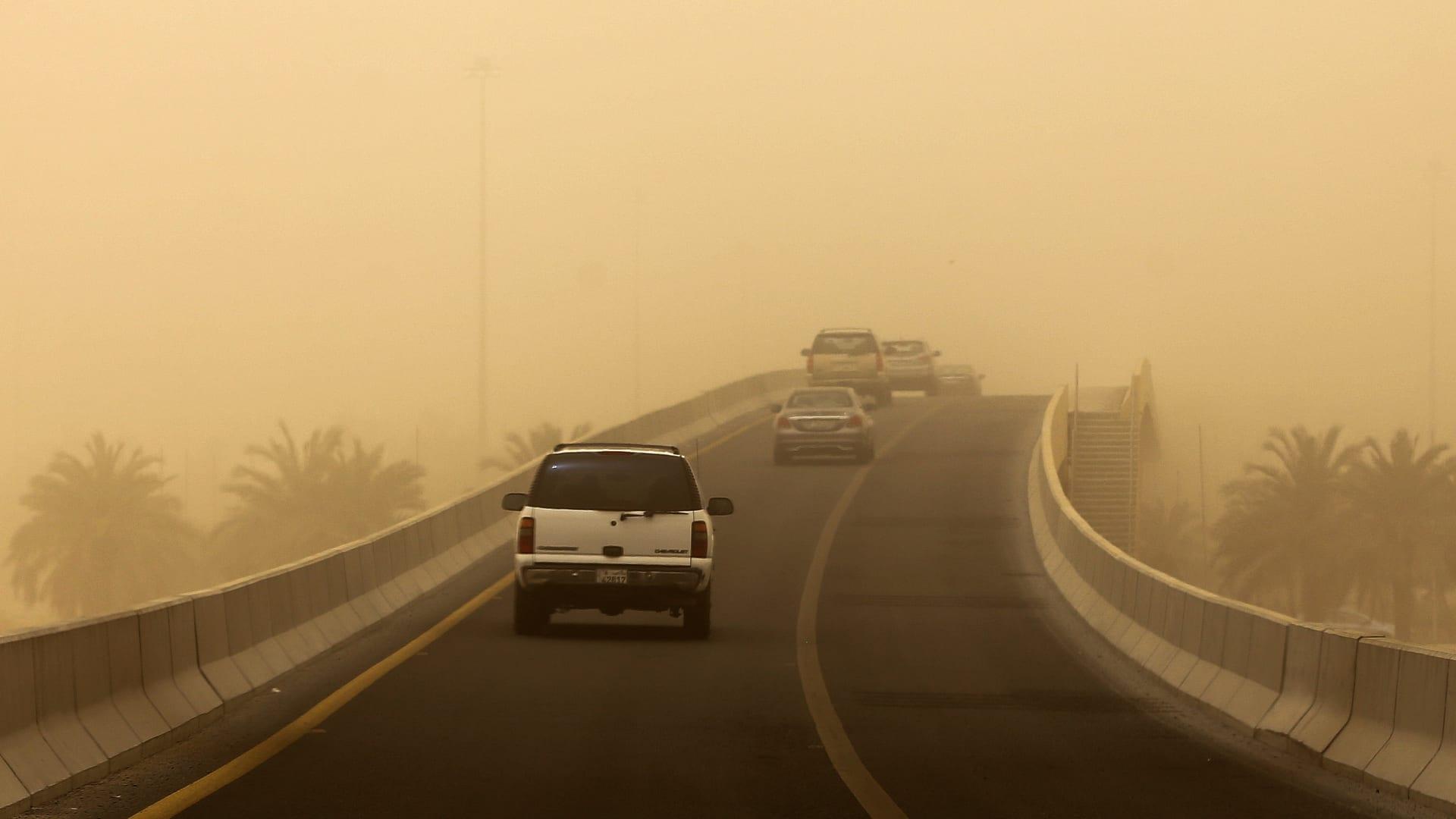 مرور المركبات خلال عاصفة رملية شديدة ضربت مدينة الكويت في 24 مايو / أيار 2017. / AFP PHOTO / ياسر الزيات