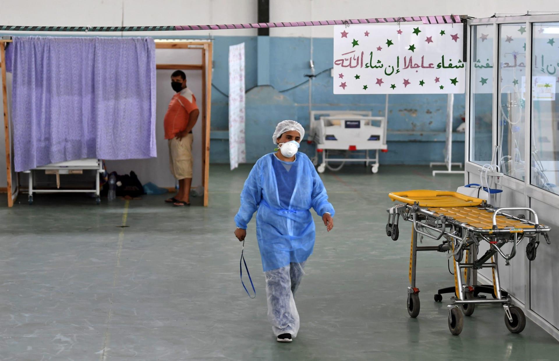 طبيبة تونسية تعتني بمريض في صالة ألعاب رياضية تم تحويلها للتعامل مع زيادة في الإصابات الجديدة بكوفيد -19 في مدينة القيروان شرق وسط البلاد في 4 يوليو 2021.