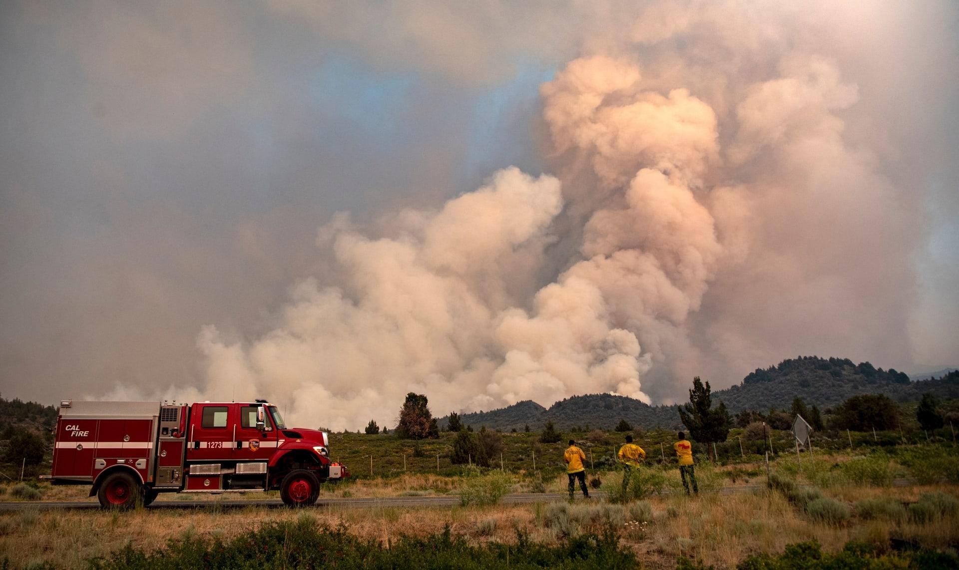 يراقب رجال الإطفاء المشهد بينما تستمر حرائق الحمم البركانية في الاشتعال في ويد بولاية كاليفورنيا في 1 يوليو 2021.